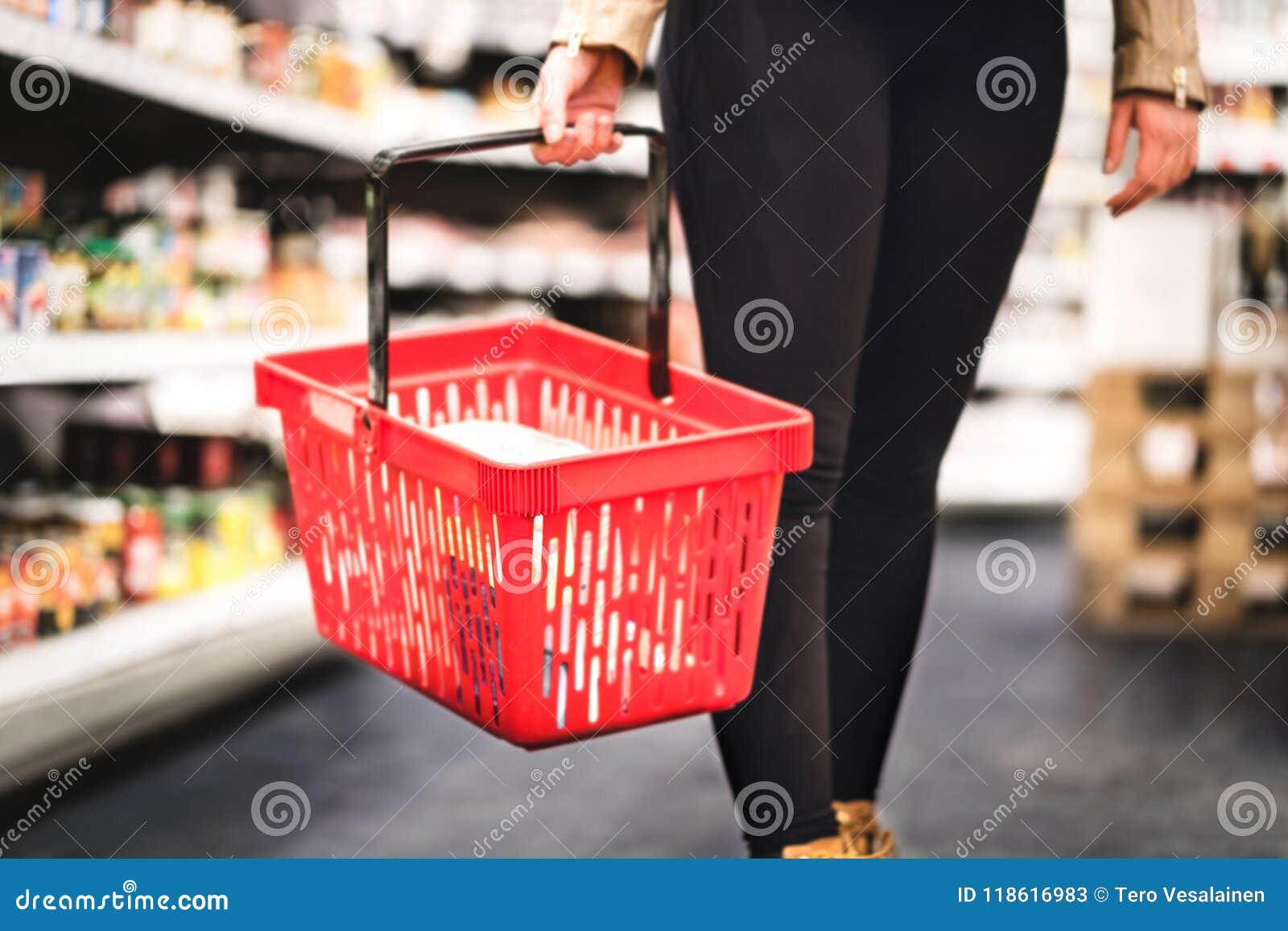 Hållande shoppingkorg för kvinna och gå i livsmedelsbutikgång