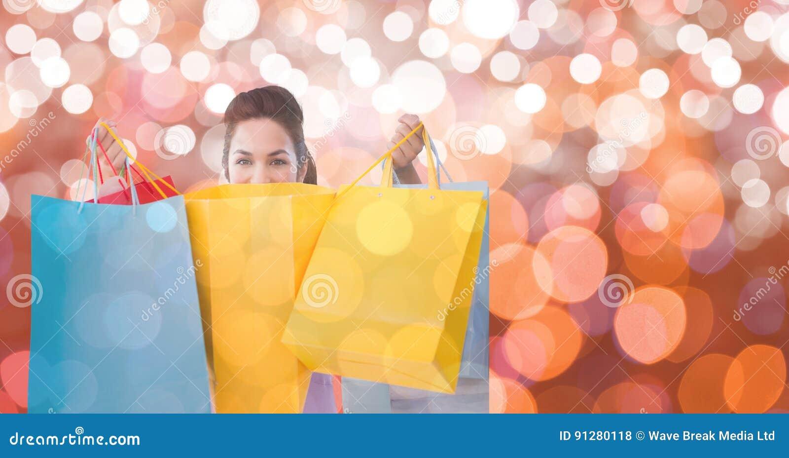Hållande shoppingpåsar för kvinna över bokeh