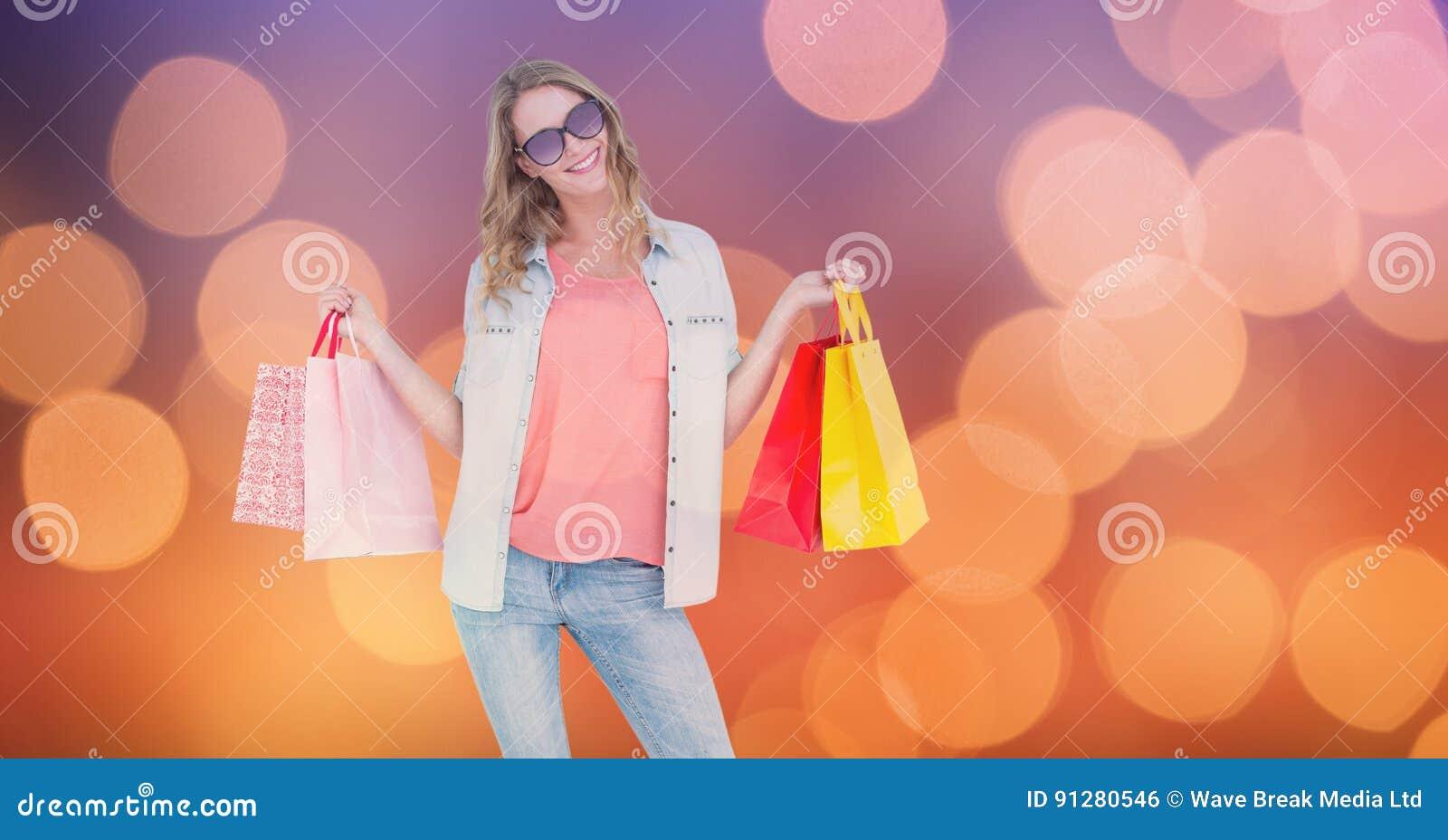 Hållande shoppingpåsar för trendig kvinna över bokeh