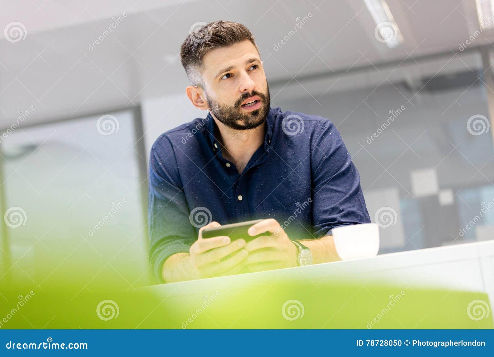 Hållande smartphone för mitt- vuxen affärsman, medan se bort i regeringsställning