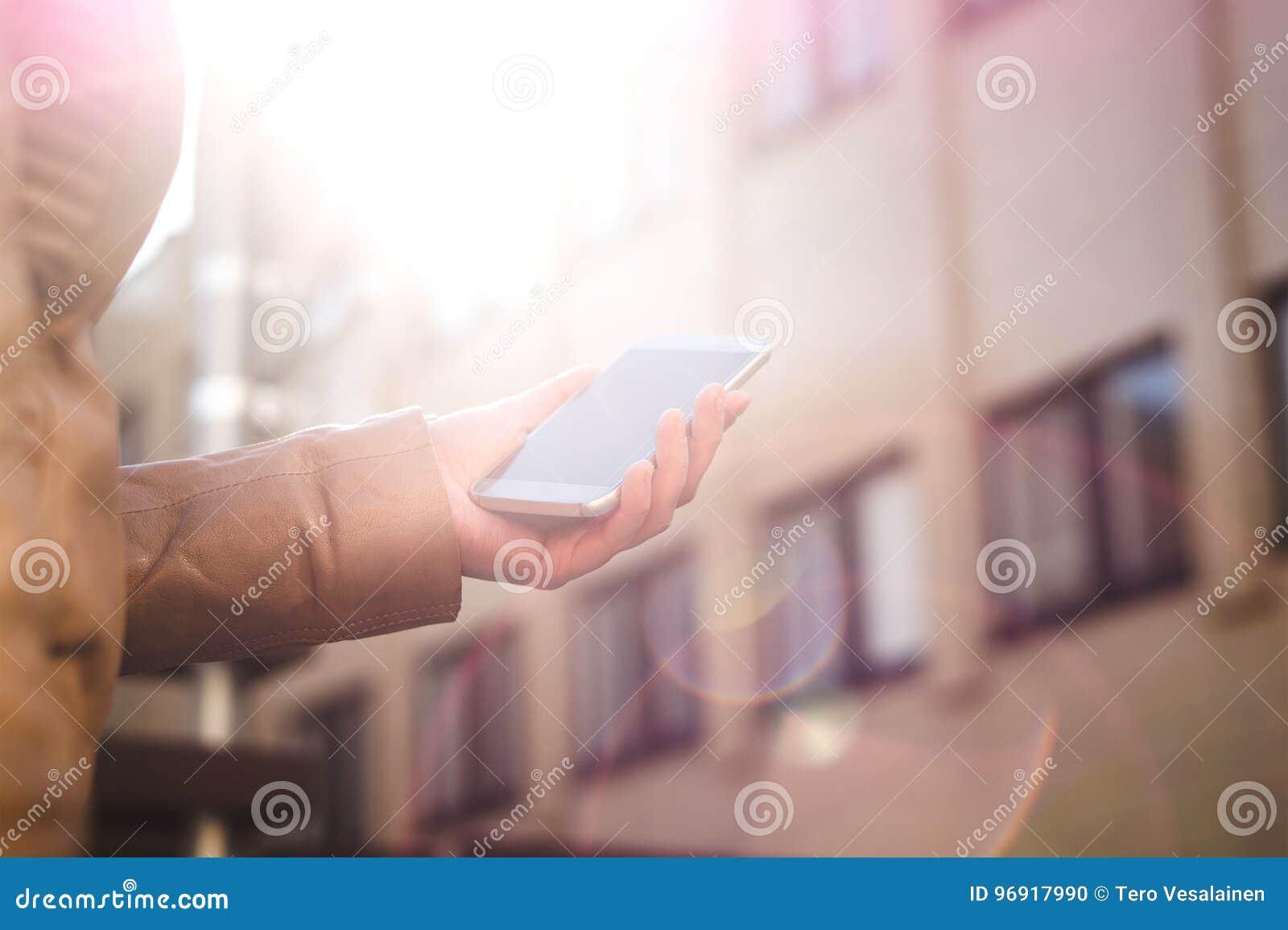 Hållande smartphone för stads- kvinna och gå i solsken Modern och moderiktig livsstil Soluppgång eller solnedgång i stadsmitten