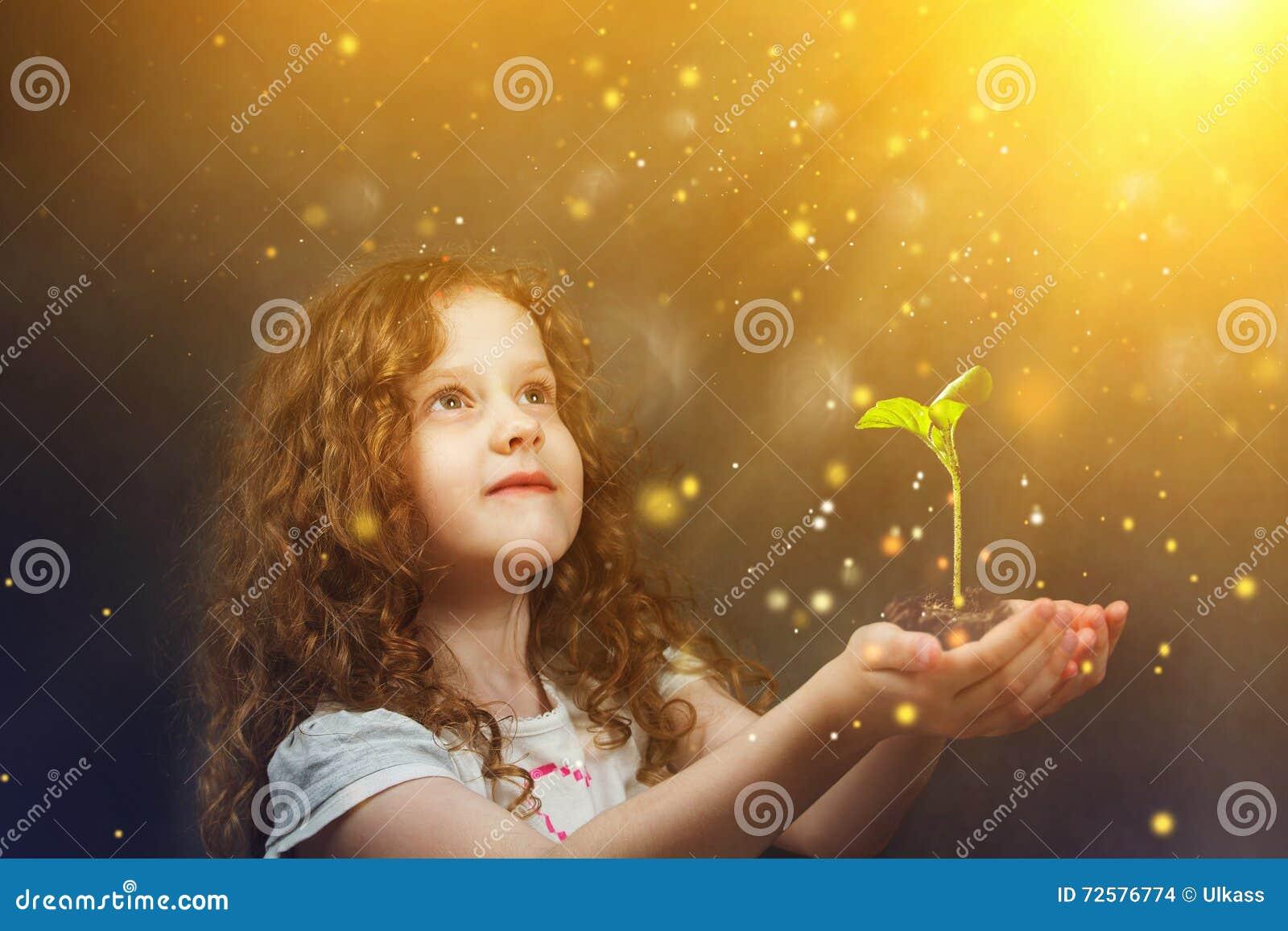 Hållande ung grön växt för liten flicka i solljus Ekologiconce