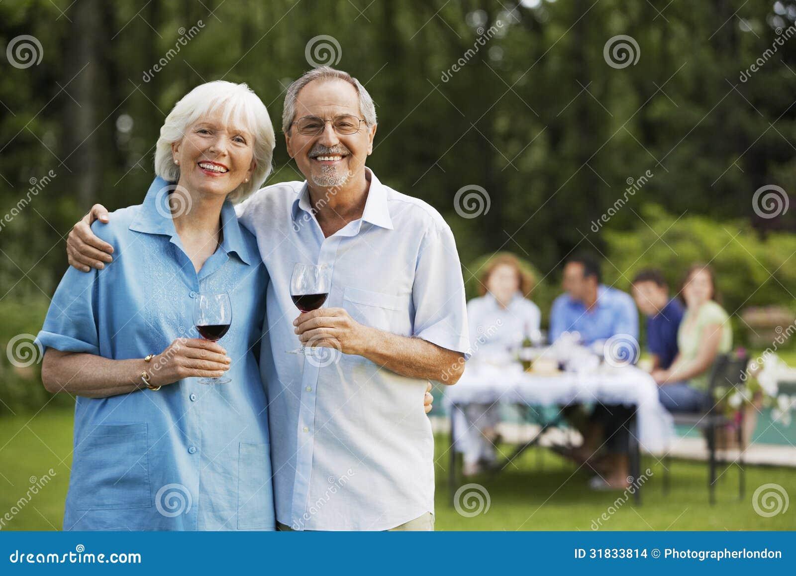 Hållande vinexponeringsglas för höga par i trädgård