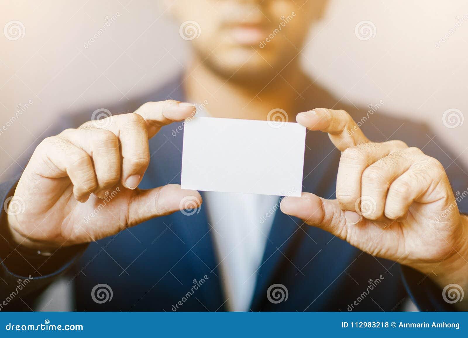 Hållande vitt affärskort för man, man som bär den blåa skjortan och visar det tomma vita affärskortet suddighet bakgrund Horisont