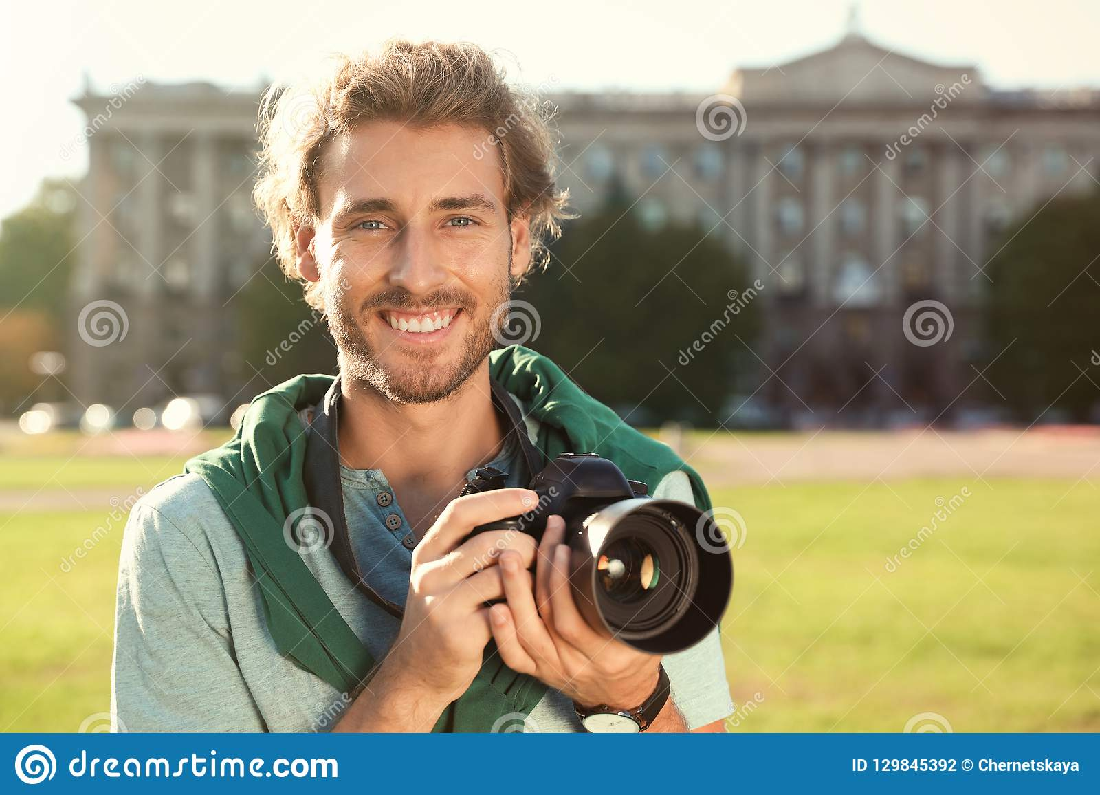 Hållande yrkesmässig kamera för ung manlig fotograf på gatan