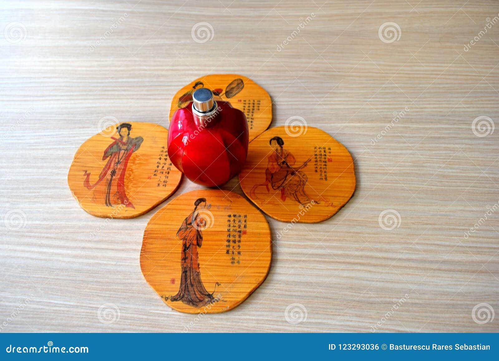 Hållare för kopp te fyra från bambus och en röd flaska av parfume i mitt