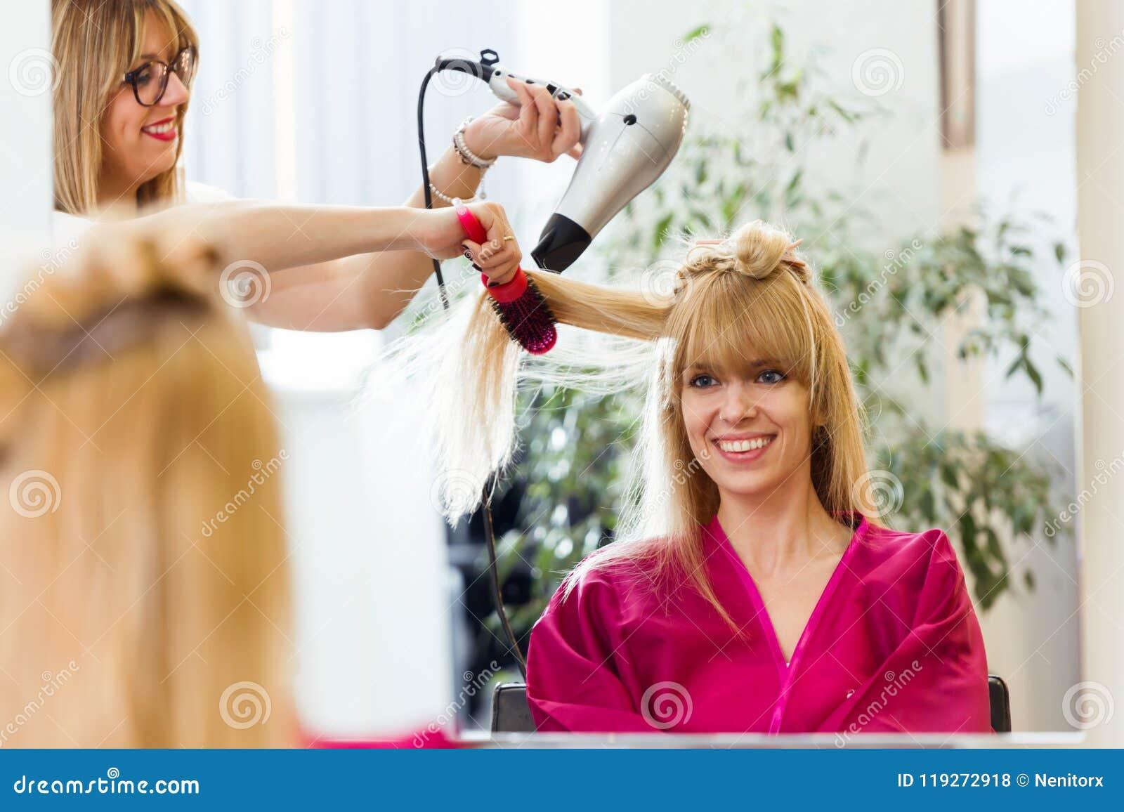 Hår för ` s för kund för frisöruttorkning kvinnligt i skönhetsalong