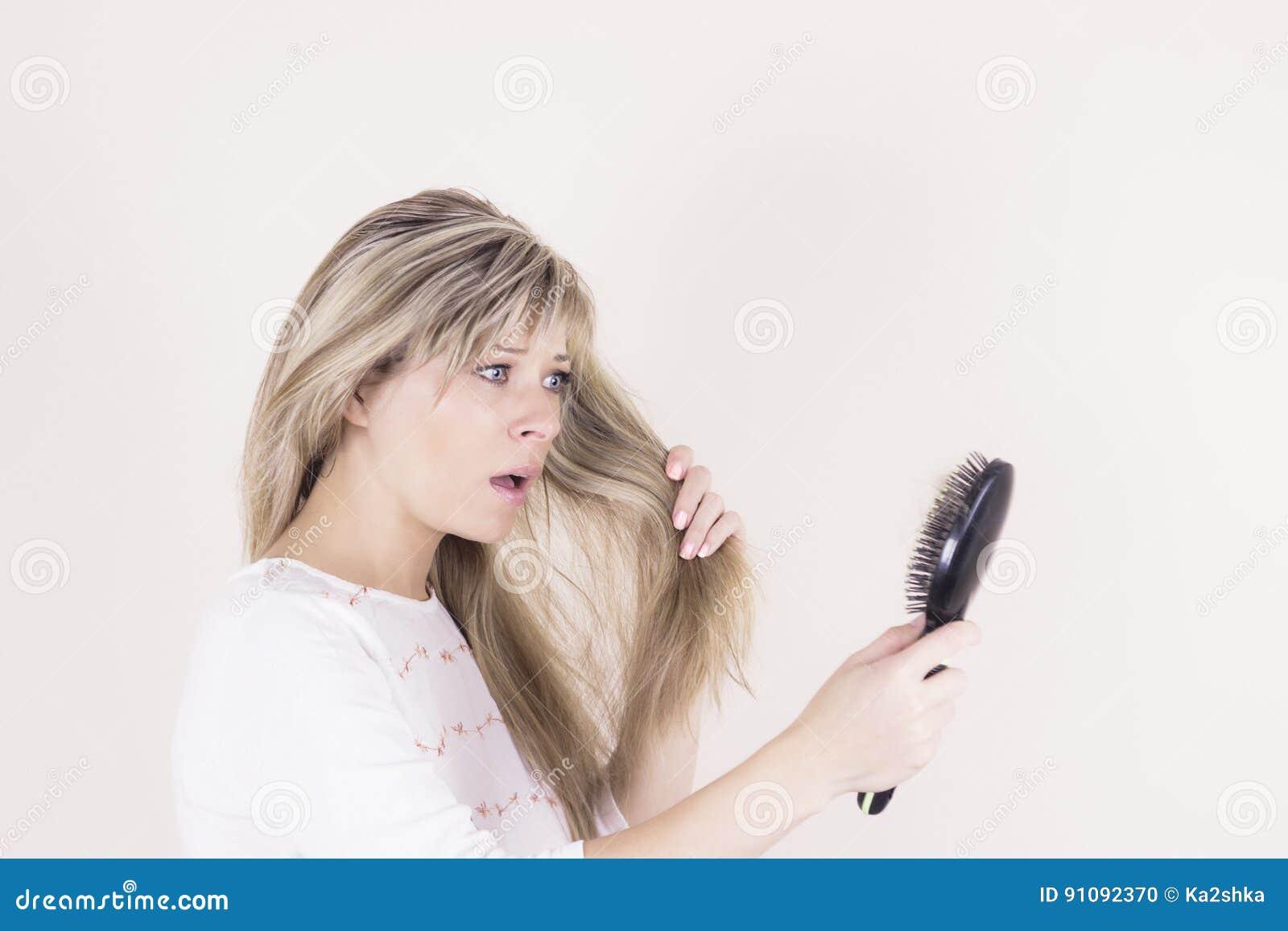 Hårförlust Deprimerad ung kvinna som ser hennes hårborste och uttrycker negativity