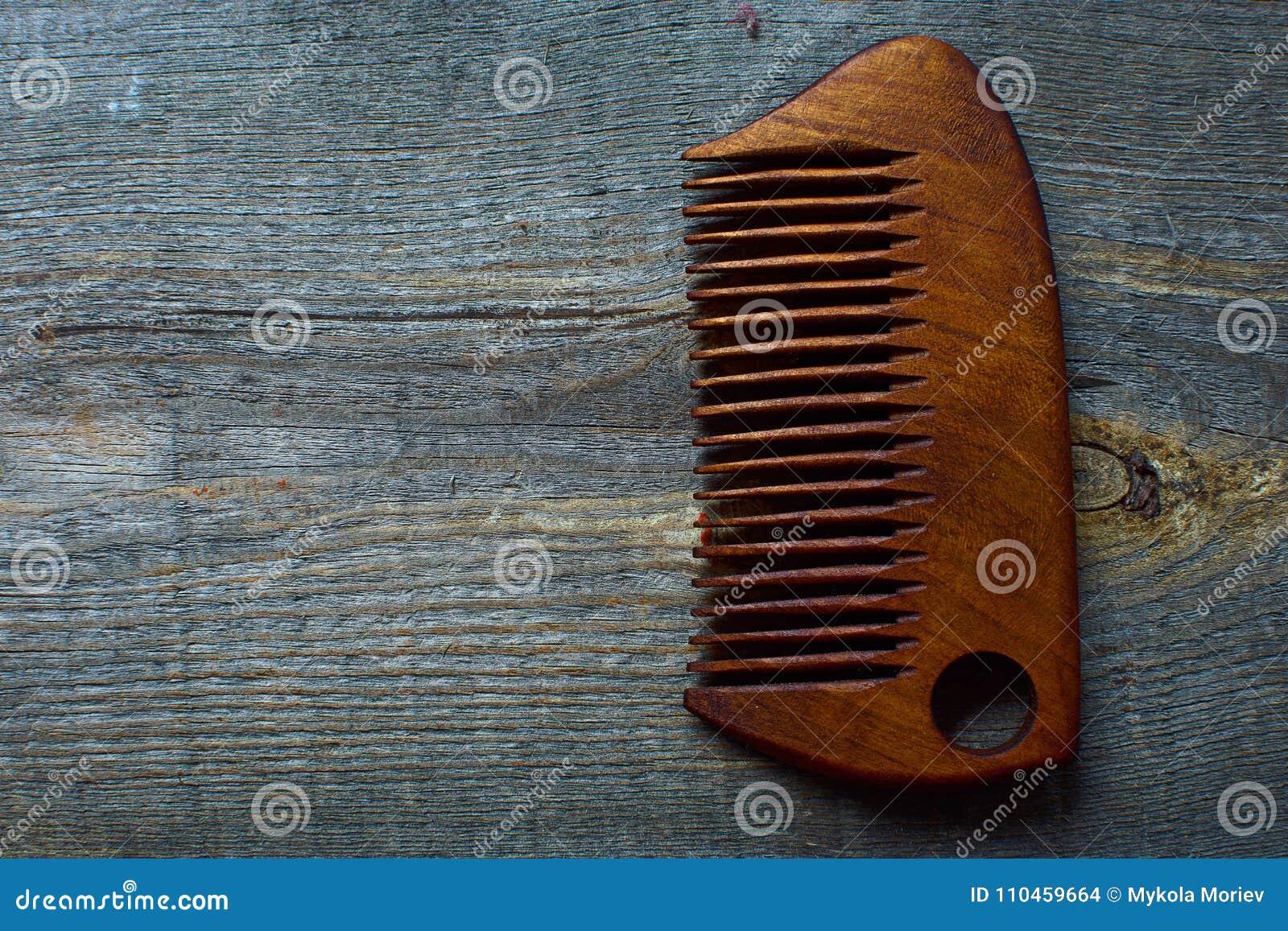 Hårkammen för ett skägg ligger på en träbakgrund