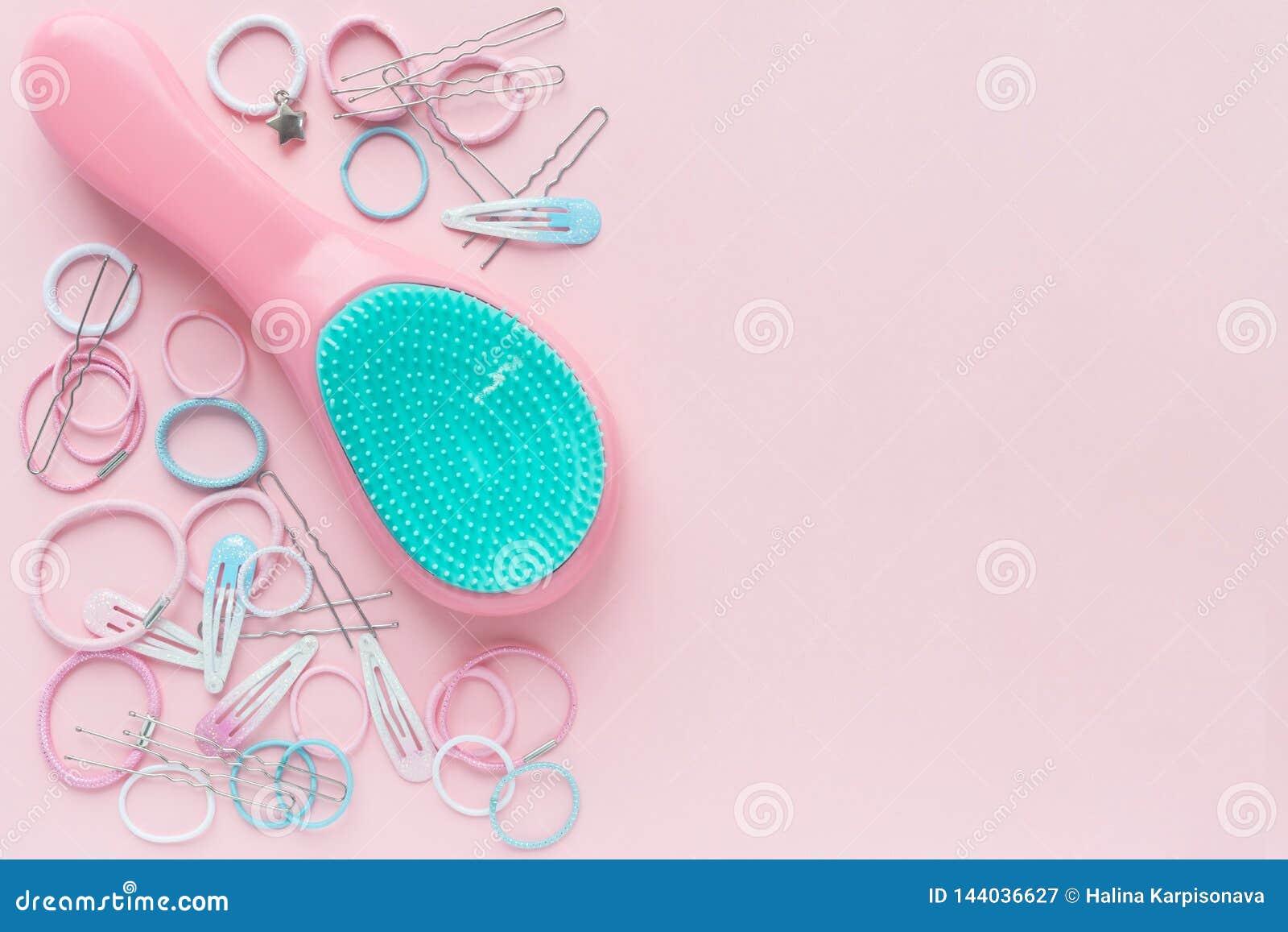 Hårscrunchies och hårnålar, hårborste på rosa bakgrund, skönhetbegrepp Lekmanna- l?genhet Fritt avst?nd f?r text