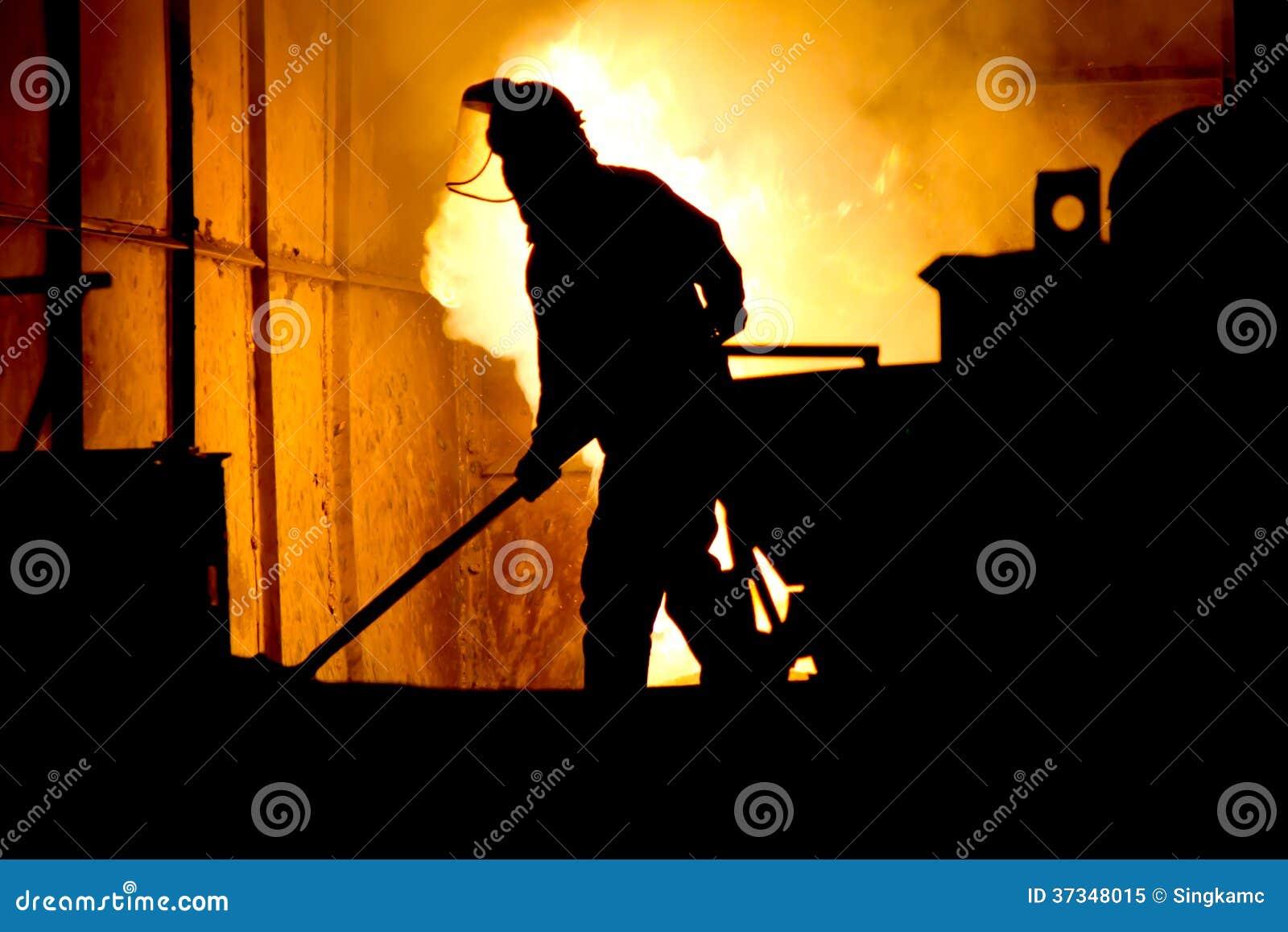 Hårt arbete i en gjuteri, smältande järn