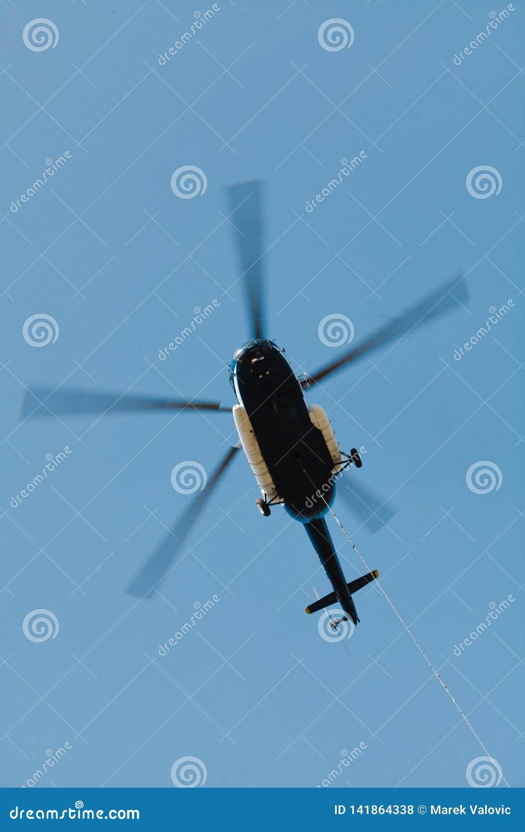 Hélicoptère de transport de fret avec du fret suspendu sur le câble - dans l action