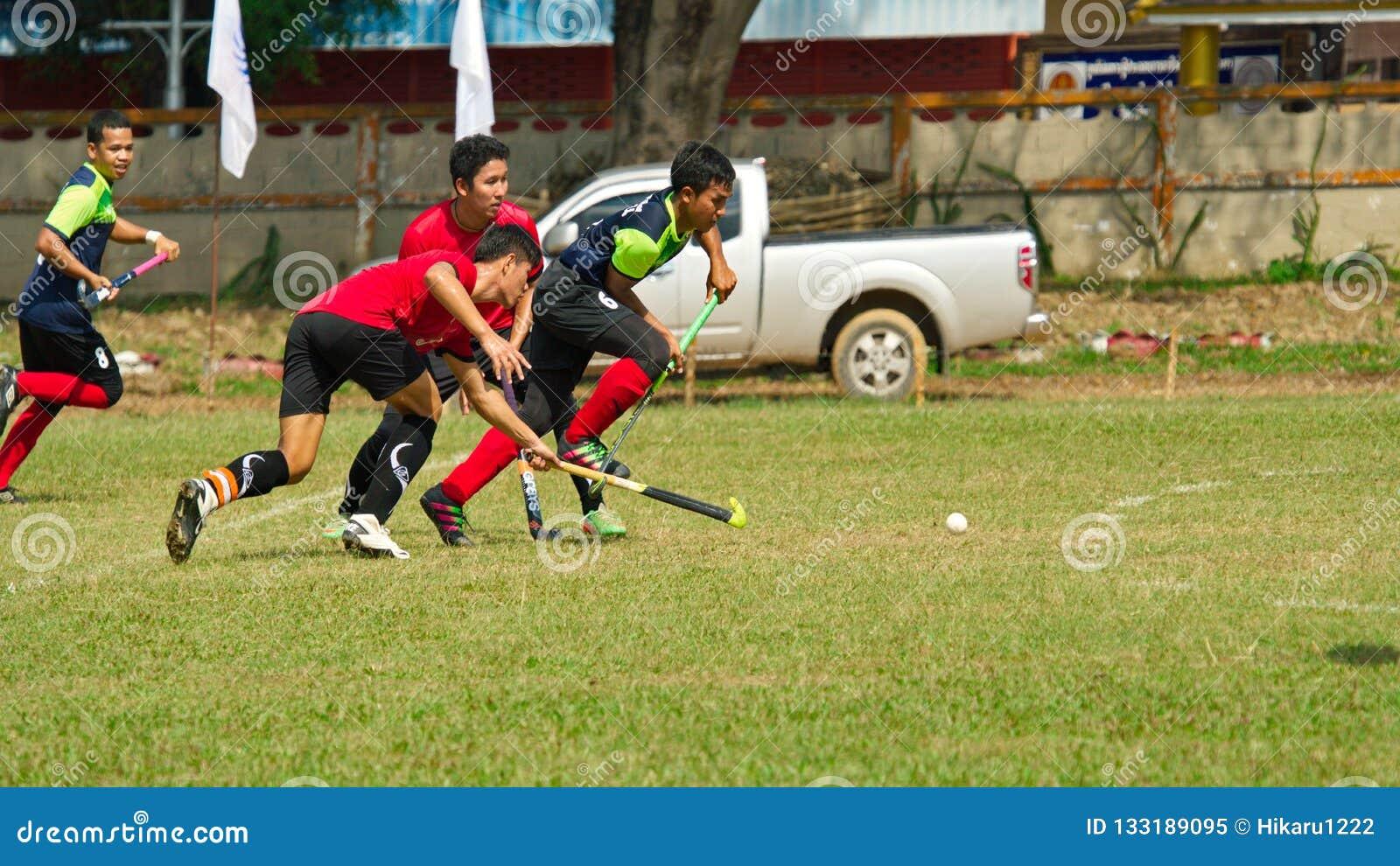 Hóquei exterior Jogador de hóquei na ação durante os jogos nacionais de Tailândia