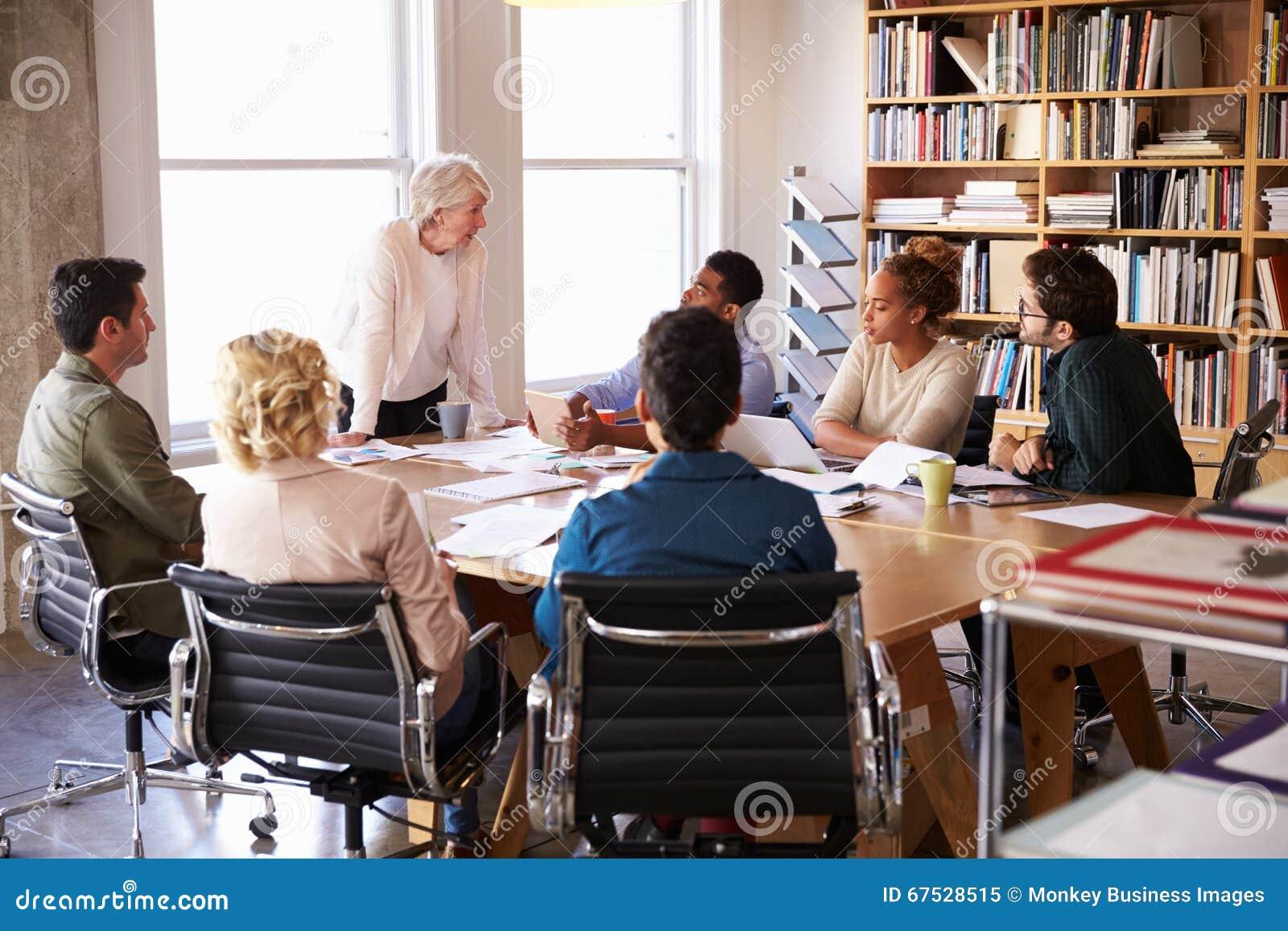 Hög affärskvinna Addressing Team Meeting Around Table