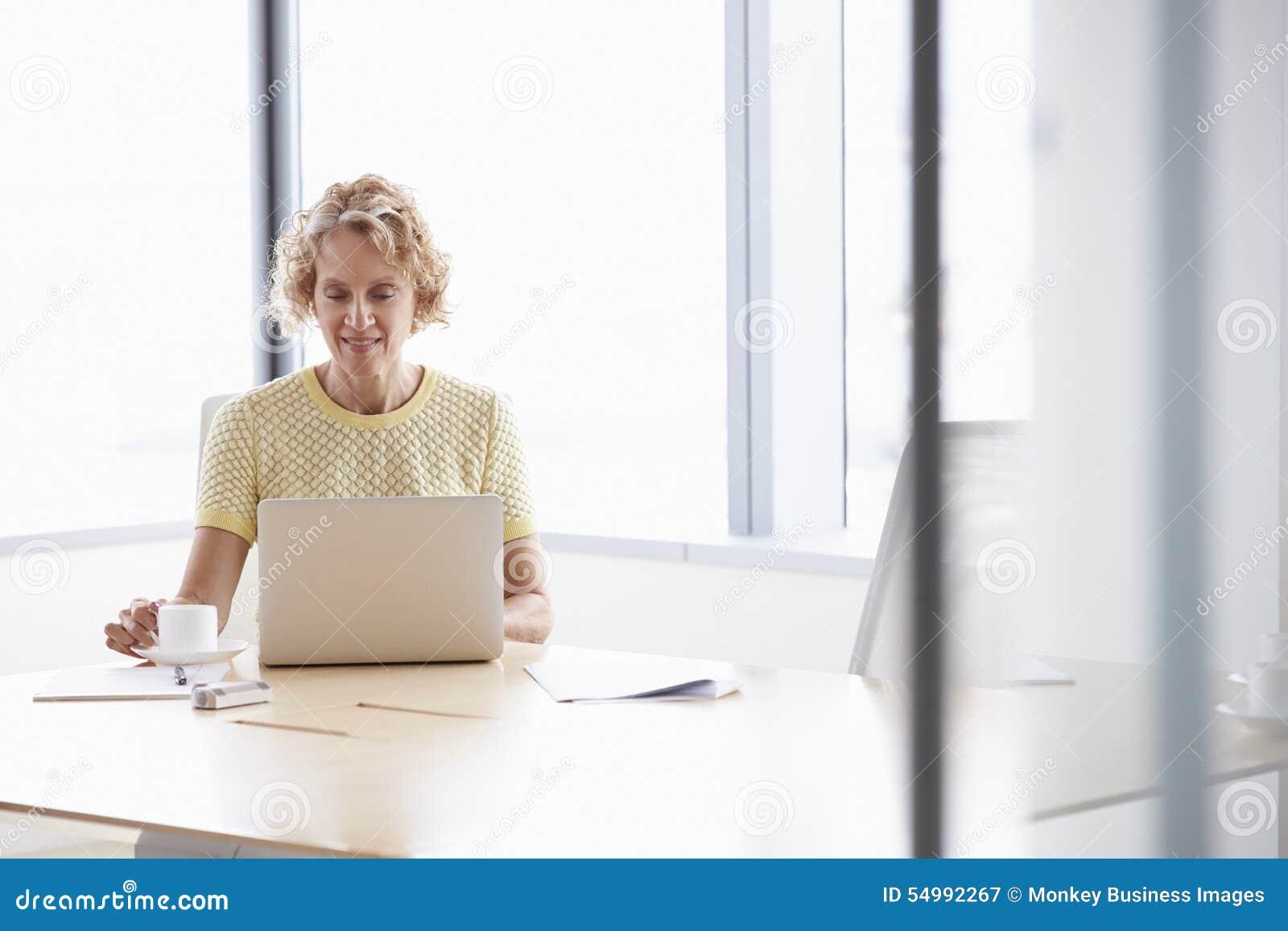 Hög affärskvinna Working On Laptop på styrelsetabellen