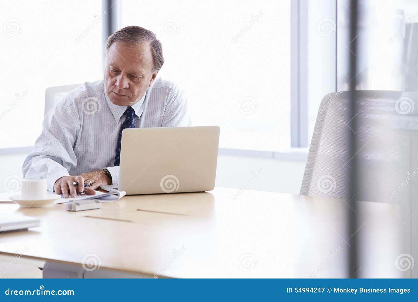 Hög affärsman Working On Laptop på styrelsetabellen