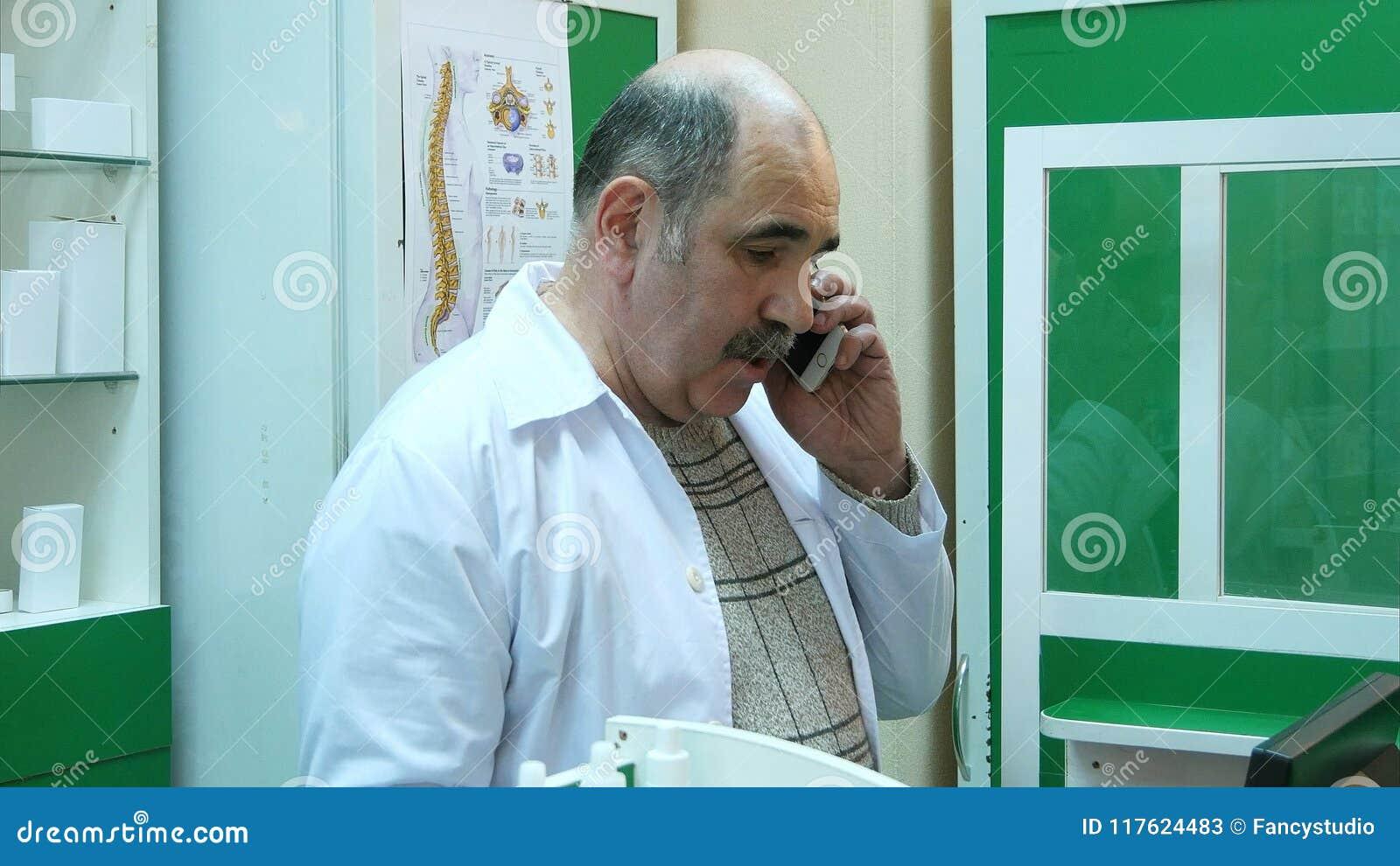 Hög apotekare som talar på mobiltelefonen, medan kontrollera receptet i apotek