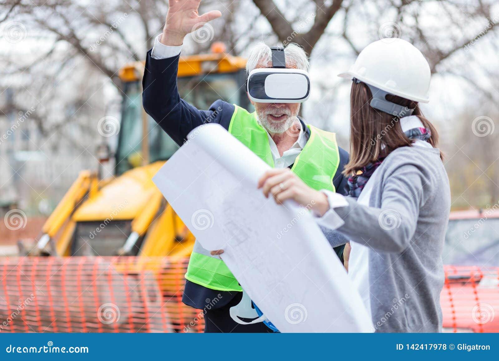 Hög arkitekt eller affärsman som använder virtuell verklighetskyddsglasögon på en konstruktionsplats