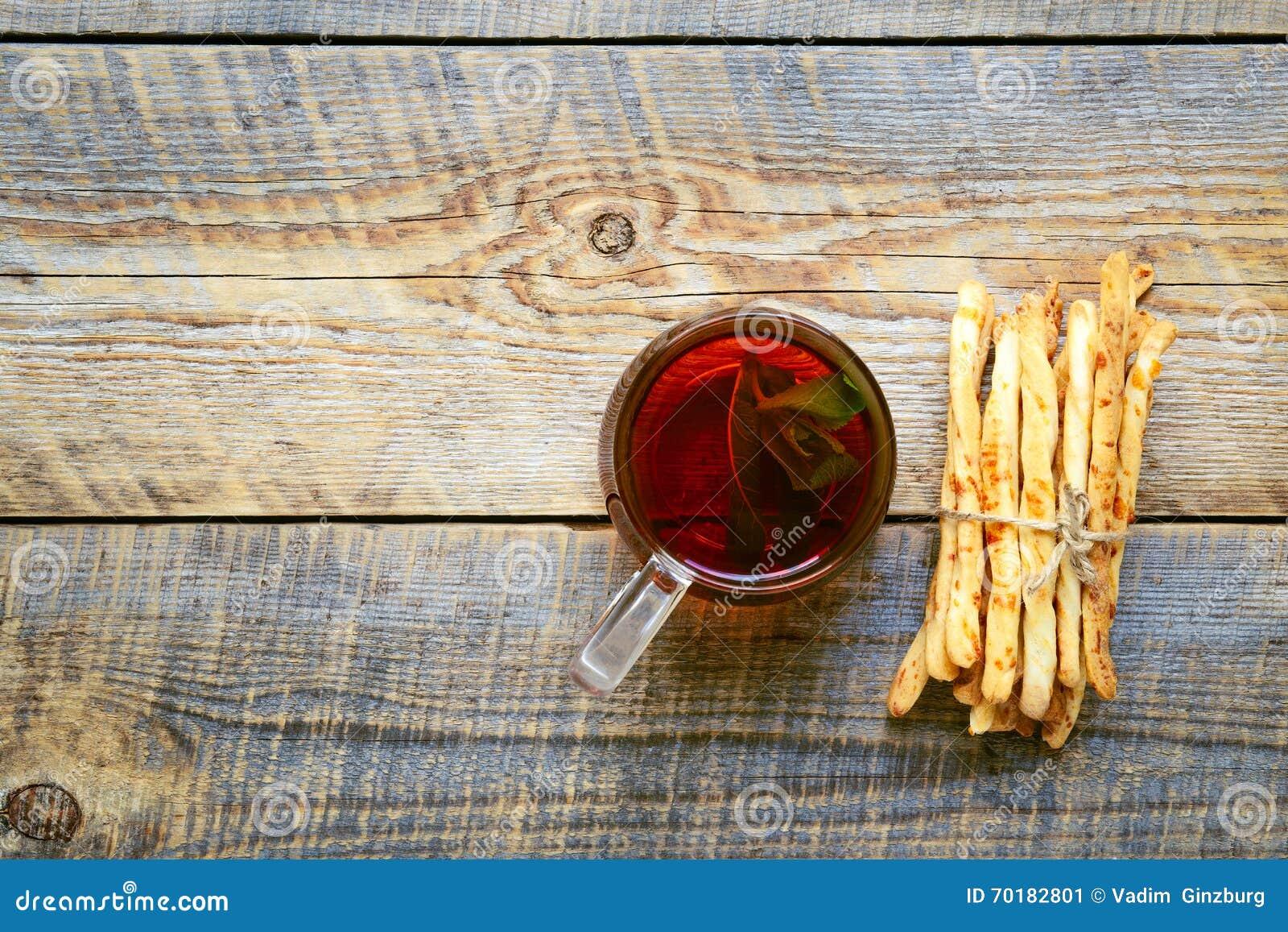 Hög av brödpinnar med te på trätabellen