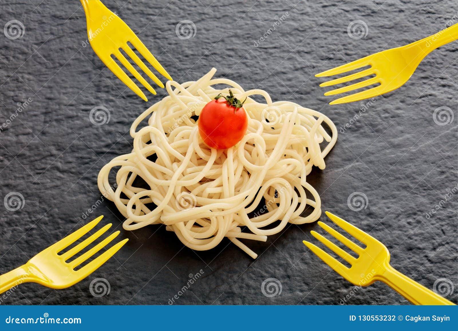 Hög av den lagade mat pastaspagetti, körsbärsröda tomaten och gafflar