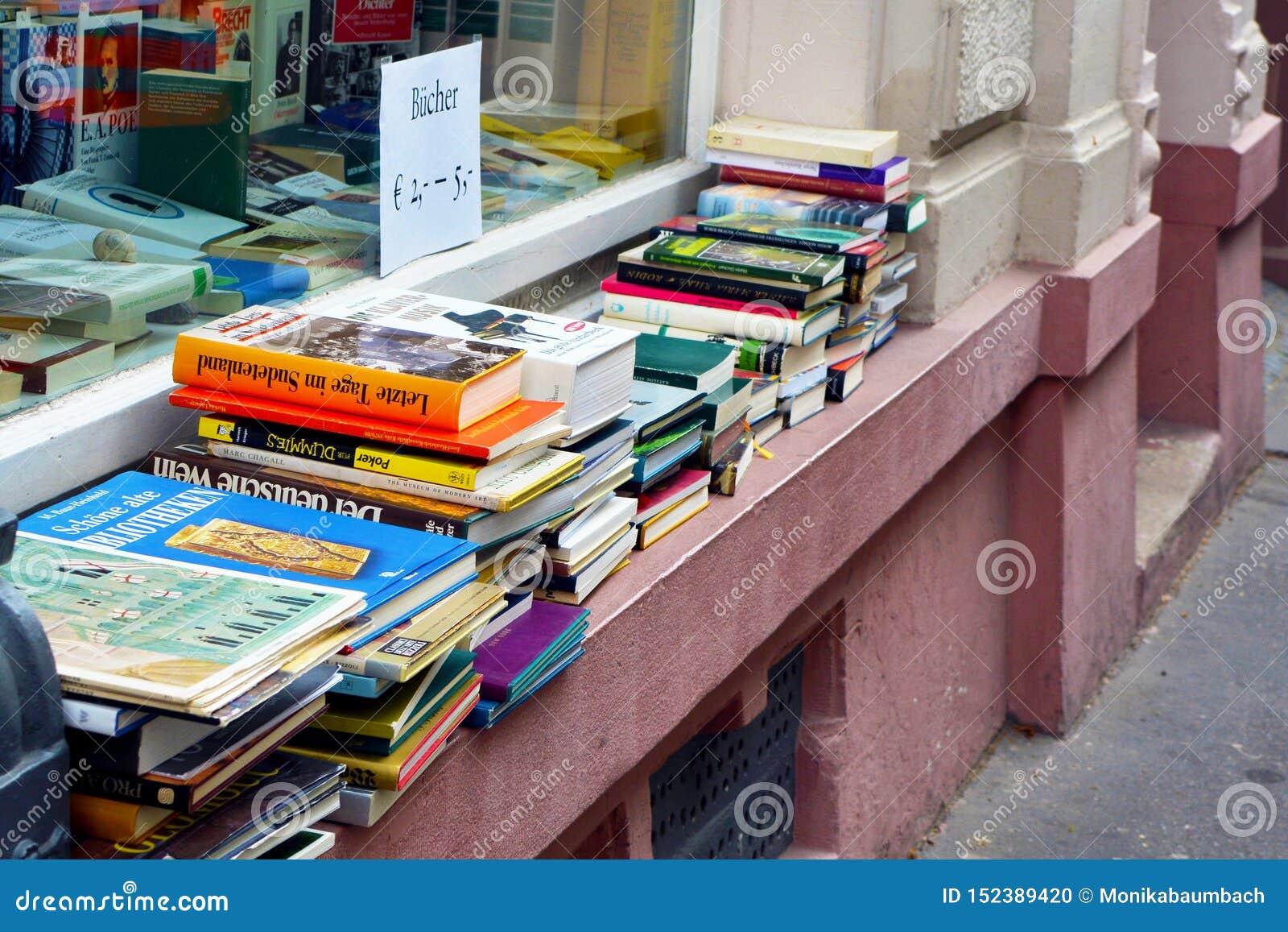 Hög av gamla använda böcker som är till salu på fönsterbräda av det använda godslagret