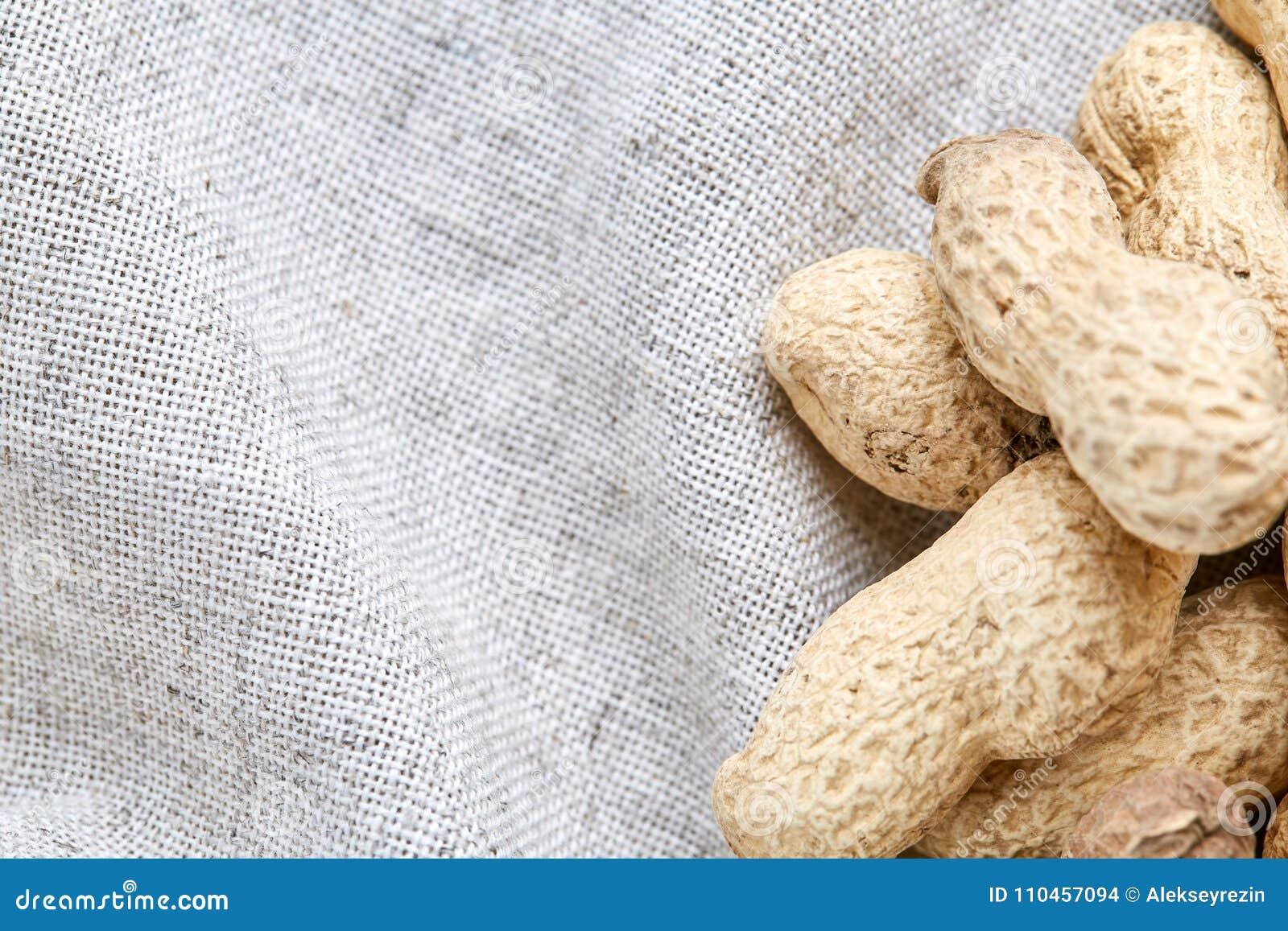 Hög av jordnötter på den ljusa bordduken, närbild, grunt djup av fältet, selektiv fokus, makro