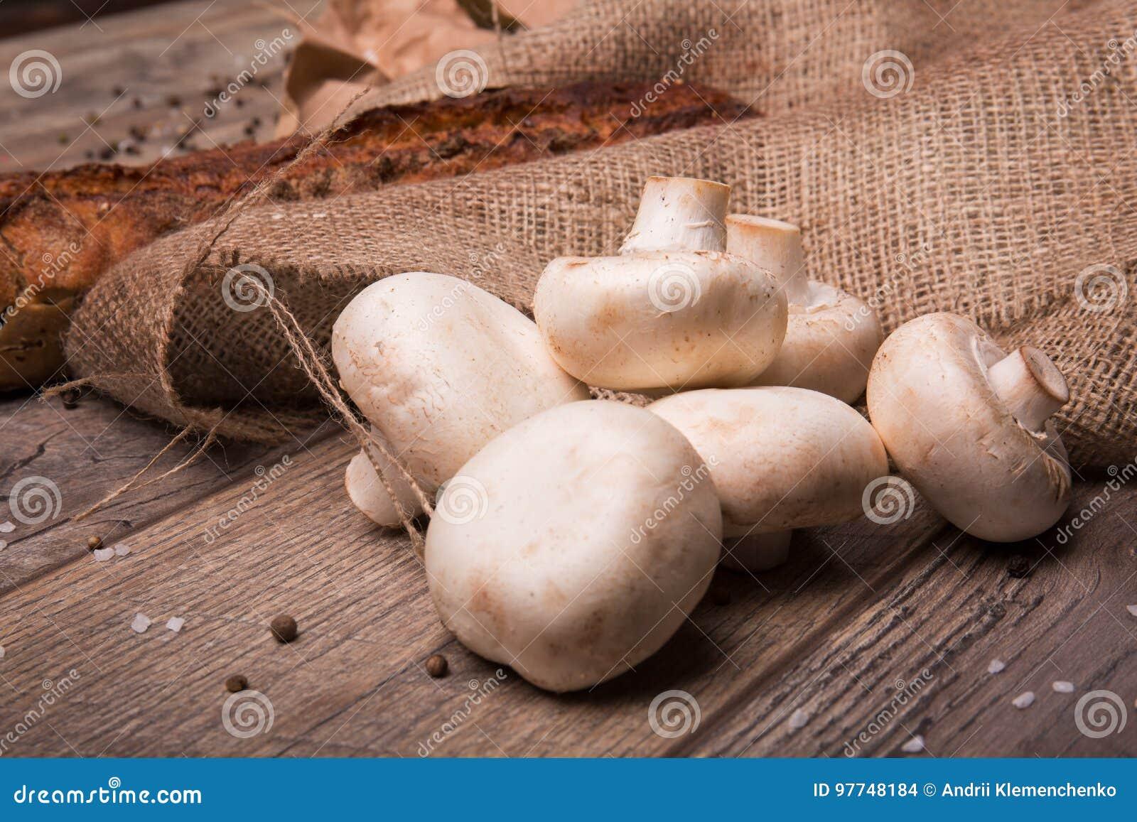 Hög av rå vita champignons och ett nytt bakat bröd på ett brunt tyg och på en träbakgrund äpplehösten undersöker torra leafs för