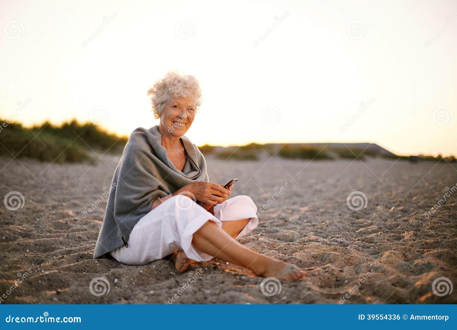 Hög caucasian kvinna med mobiltelefonen på stranden