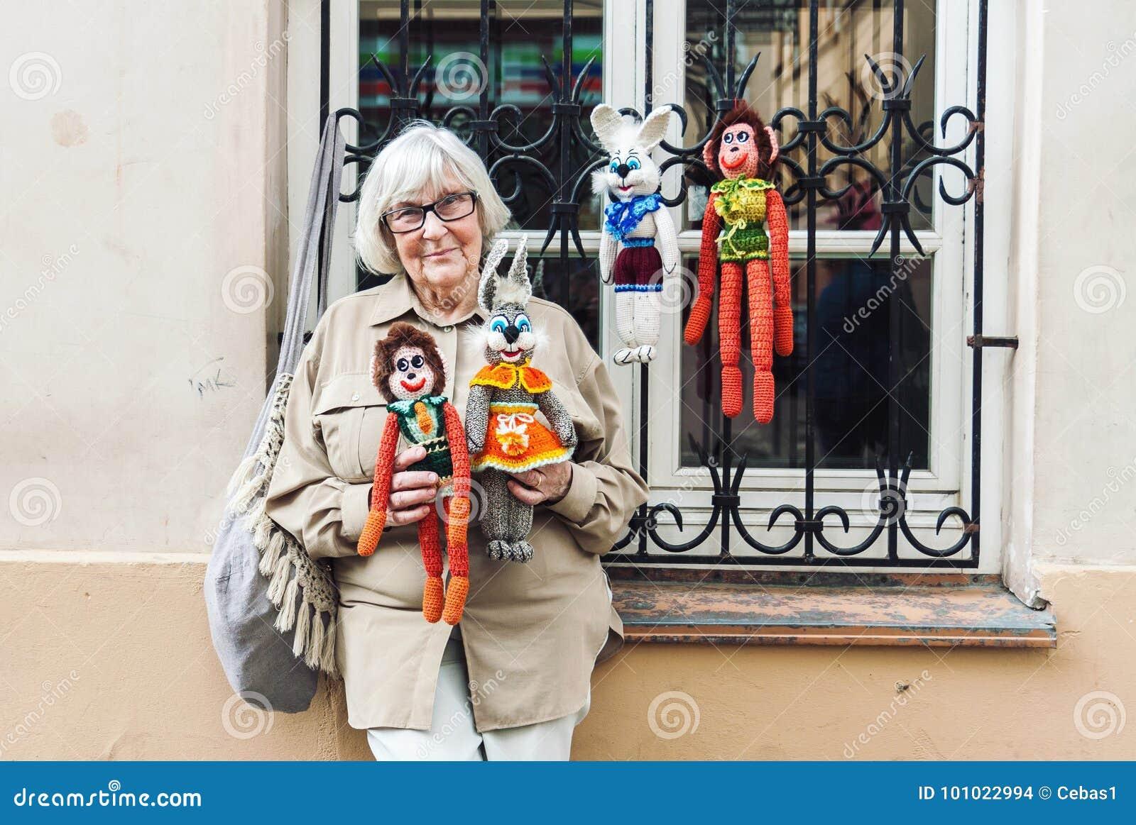 Hög dam som säljer handgjorda stack leksaker på gatan