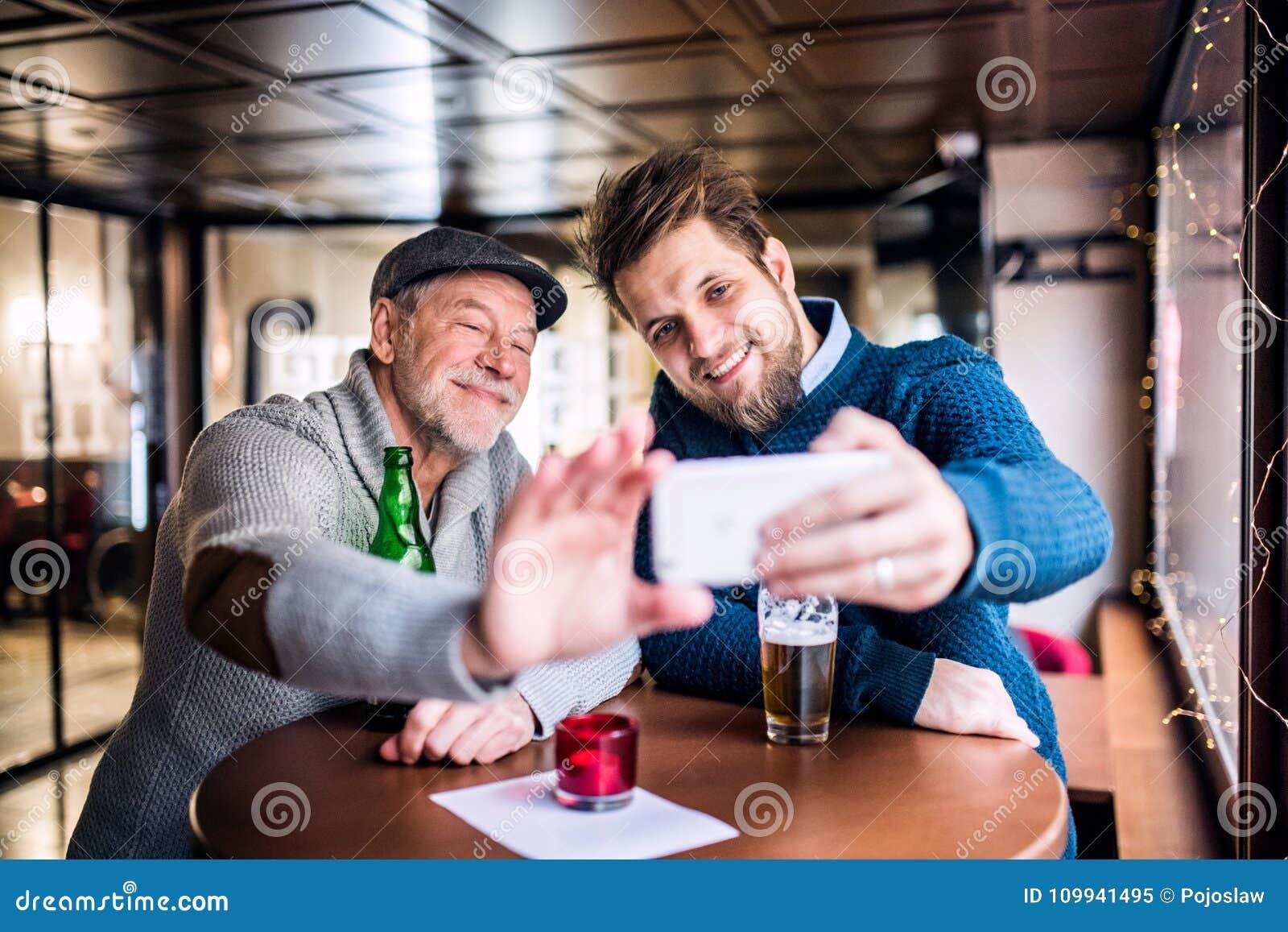 Hög fader och hans unga son med smartphonen i en bar