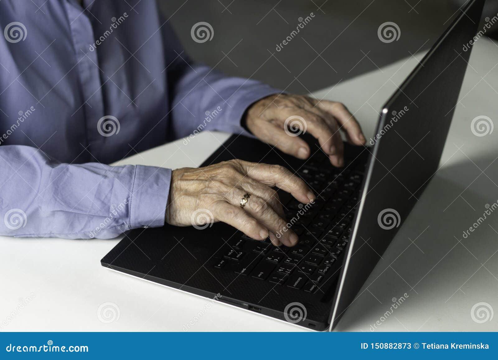 Hög gråhårig kvinna med bärbara datorn Äldre kvinnahandstilkorta avhandlingar på bärbara datorn som söker för information på inte