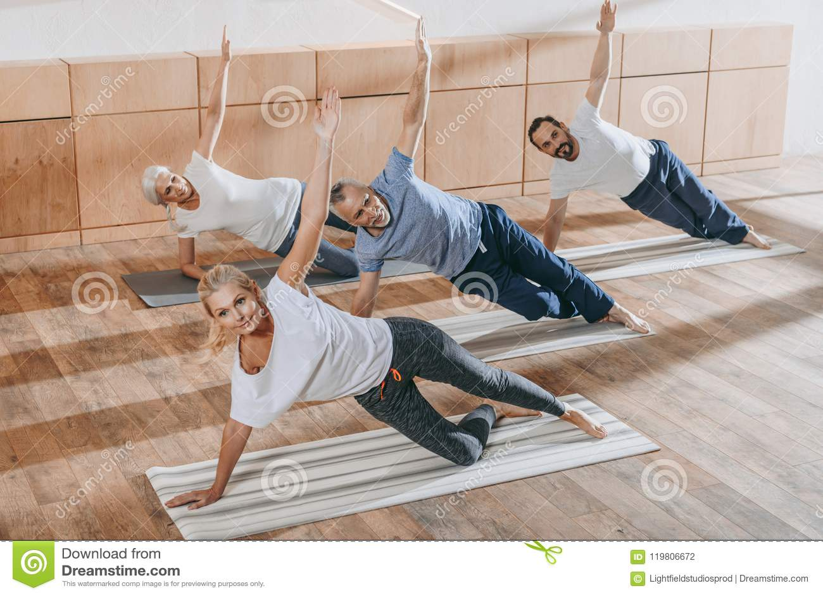 Hög grupp människor med instruktören som övar på yogamats