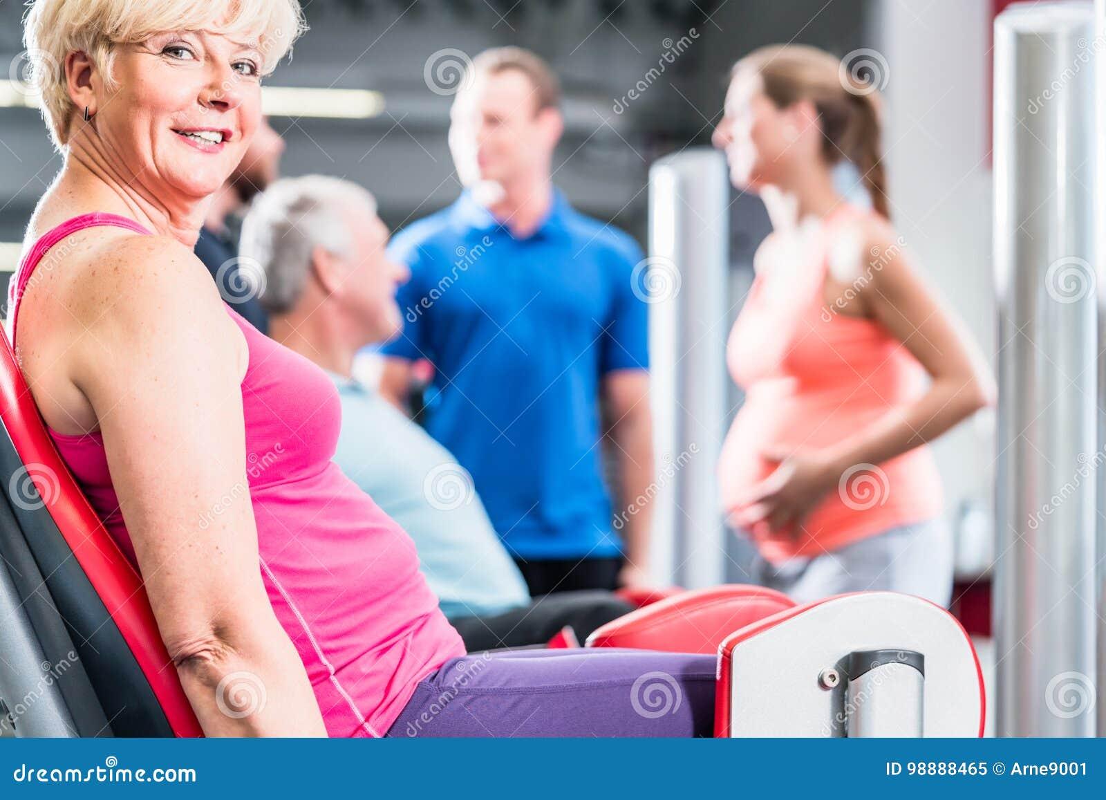 Hög kvinna i grupp med gravida kvinnan som utarbetar på idrottshallen