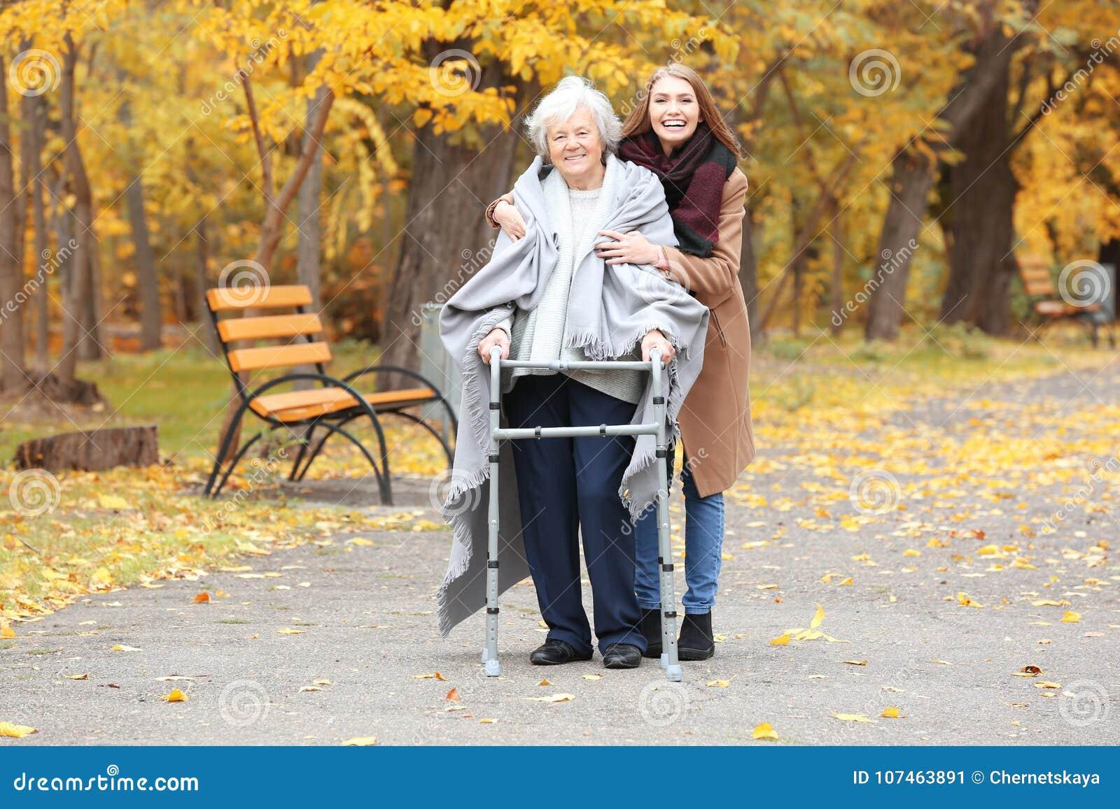 Hög kvinna med att gå ram- och barnanhörigvårdaren