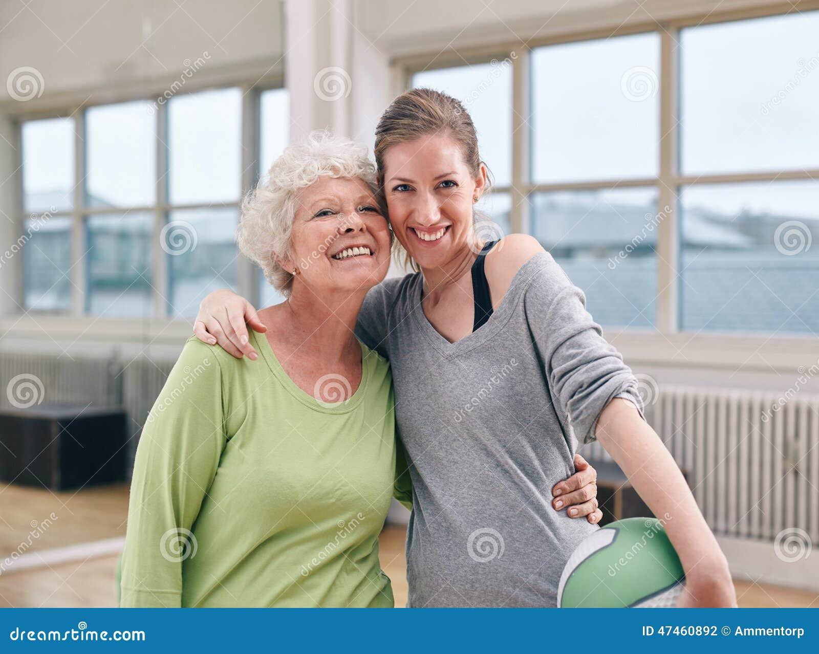 Hög kvinna med hennes personliga instruktör på idrottshallen