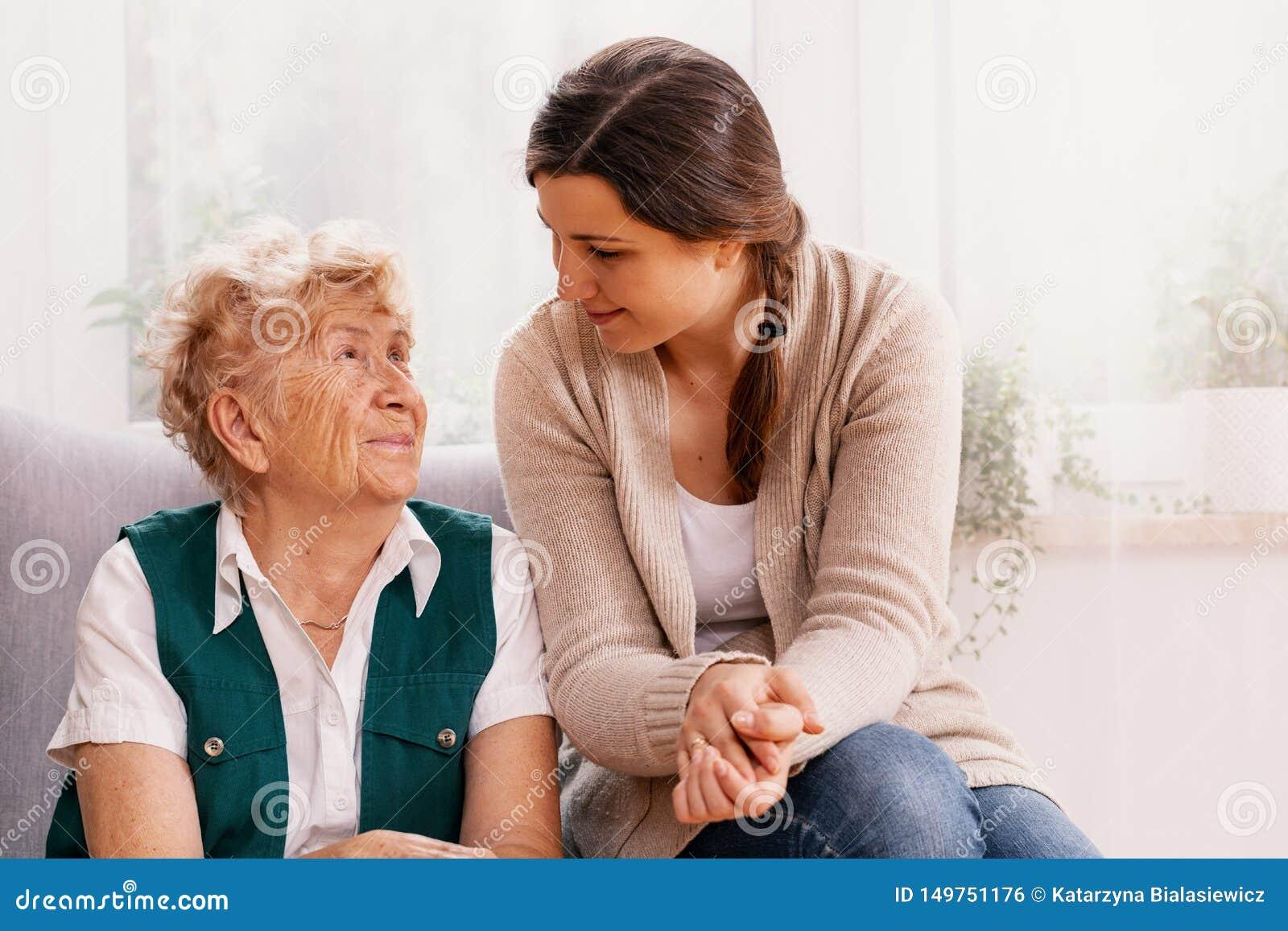 Hög kvinna och hjälpsam volontär på vårdhemmet