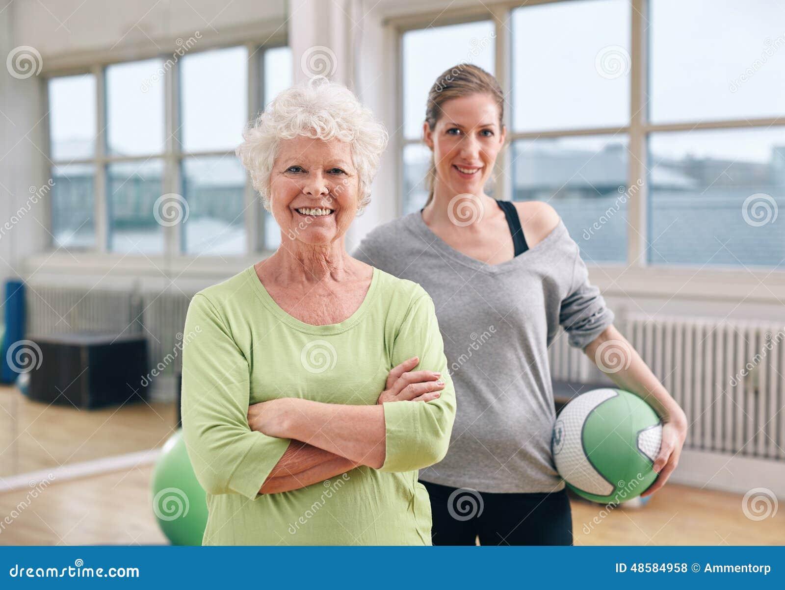Hög kvinna på den vård- klubban med idrottshallinstruktören
