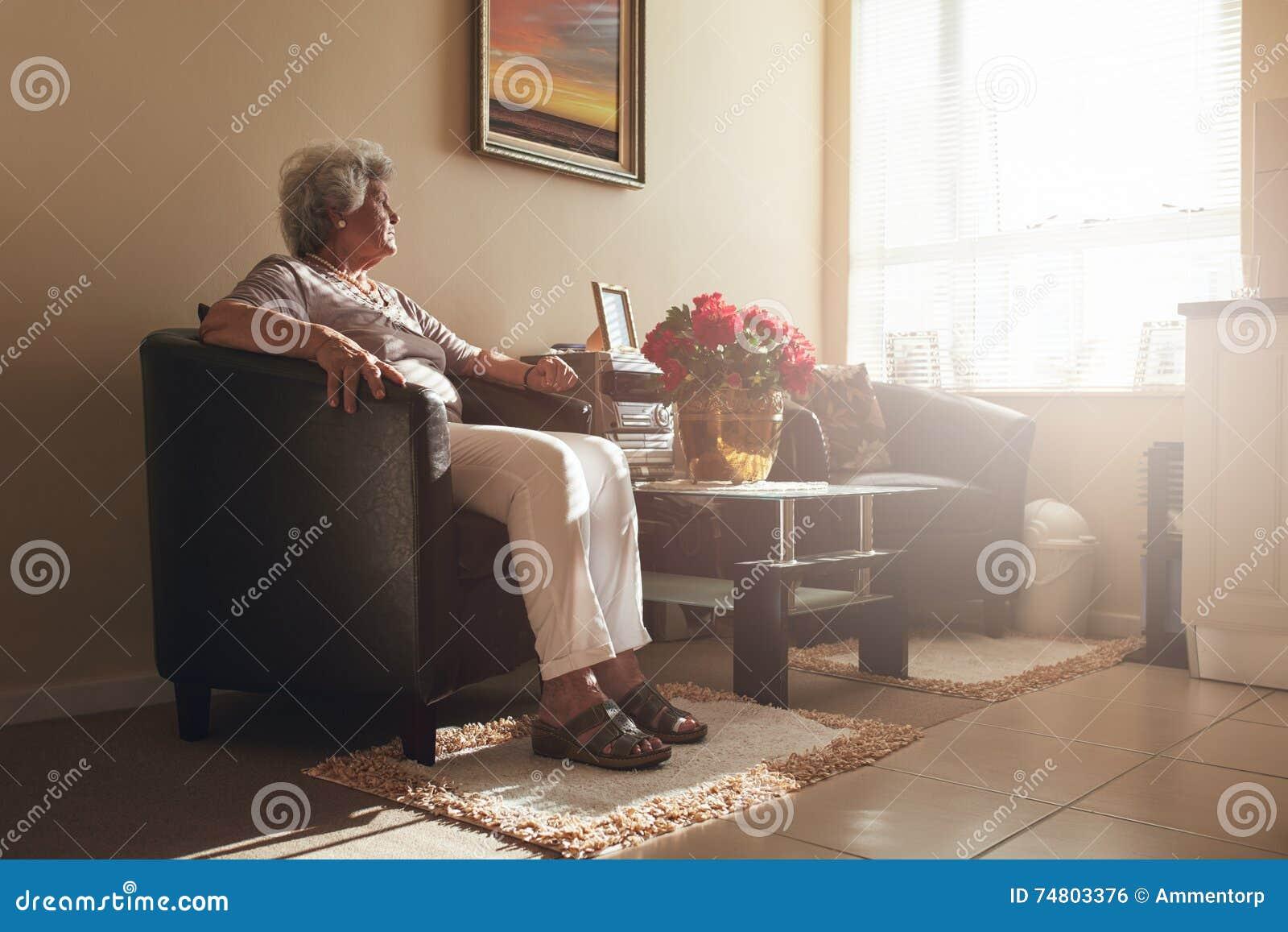 Hög kvinna som bara hemma sitter på en stol