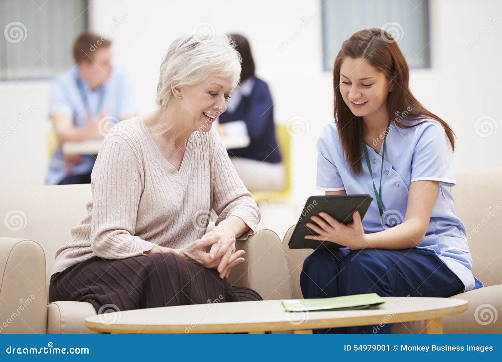 Hög kvinna som diskuterar provresultat med sjuksköterskan