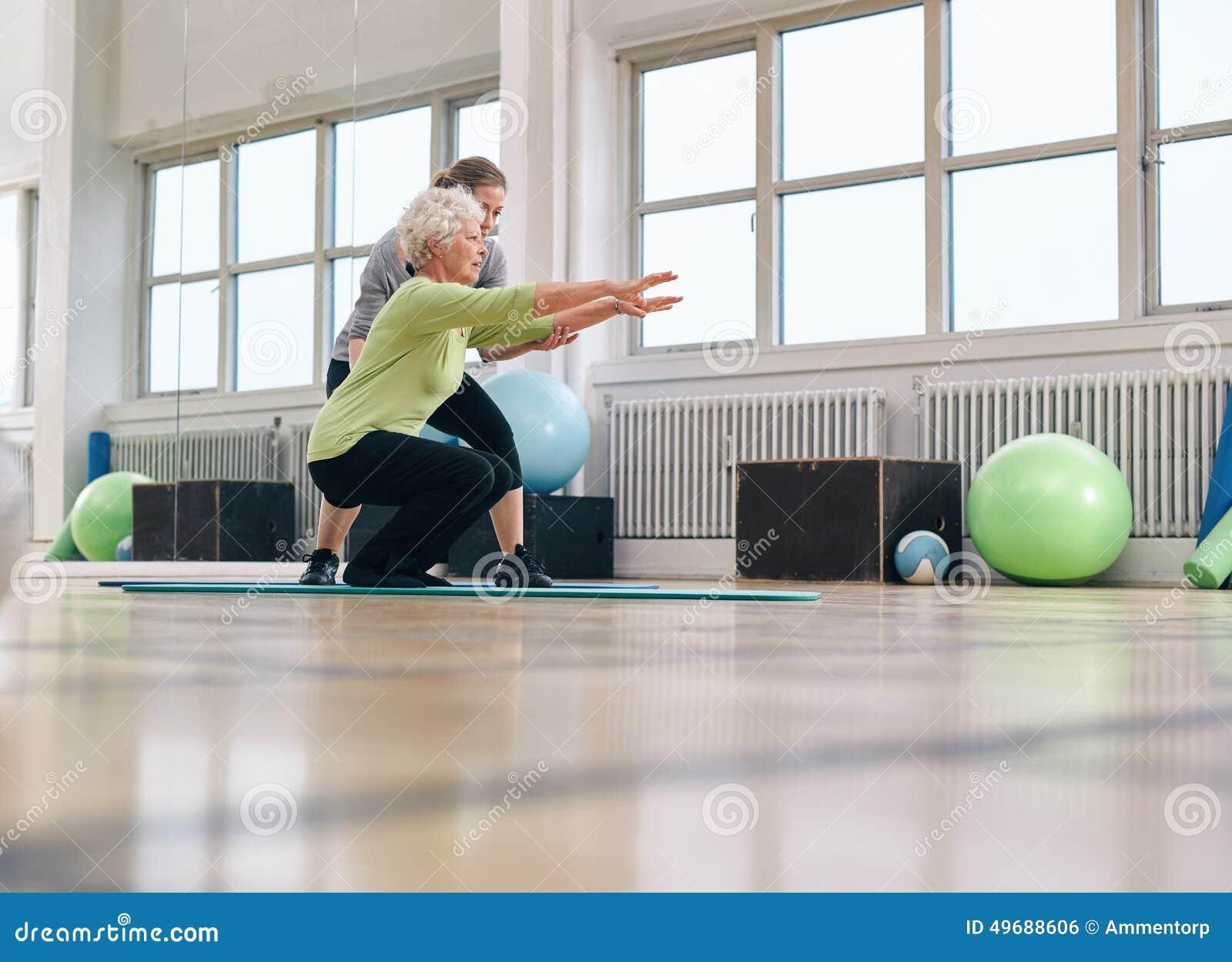 Hög kvinna som gör övning med hennes personliga instruktör