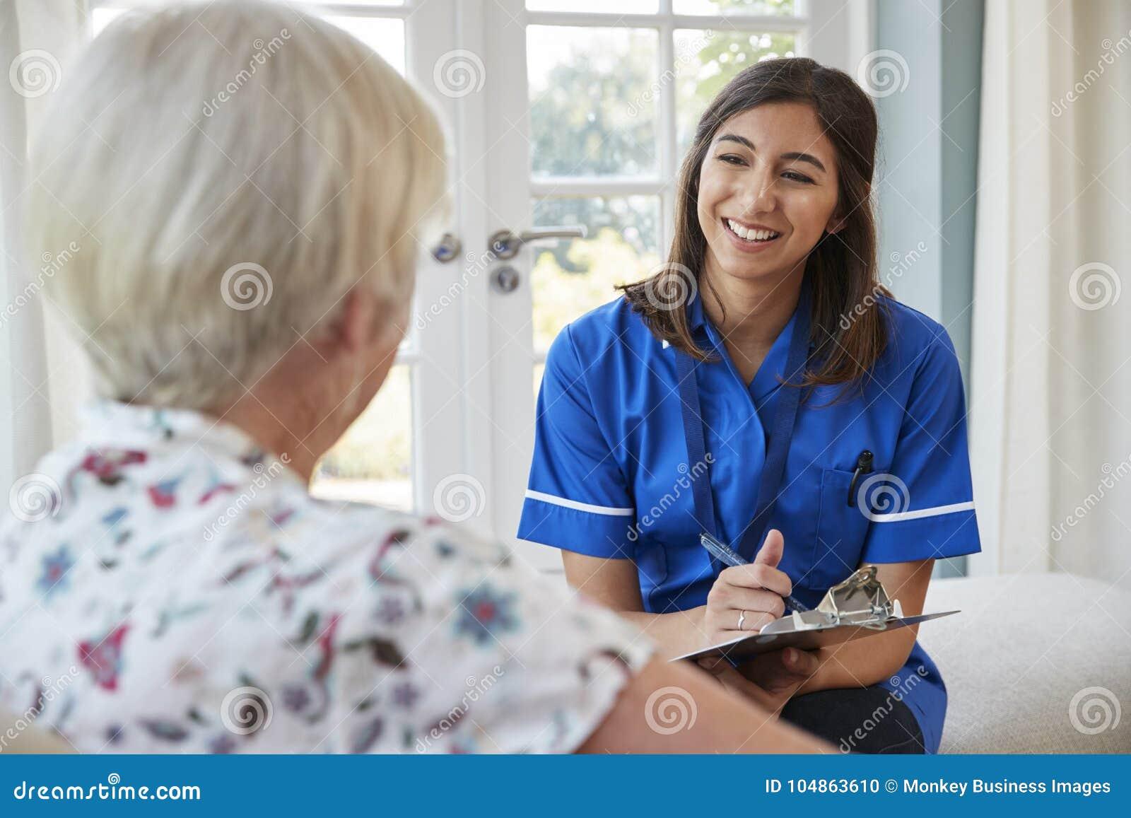 Hög kvinna som hemma sitter med omsorgsjuksköterskan som tar anmärkningar