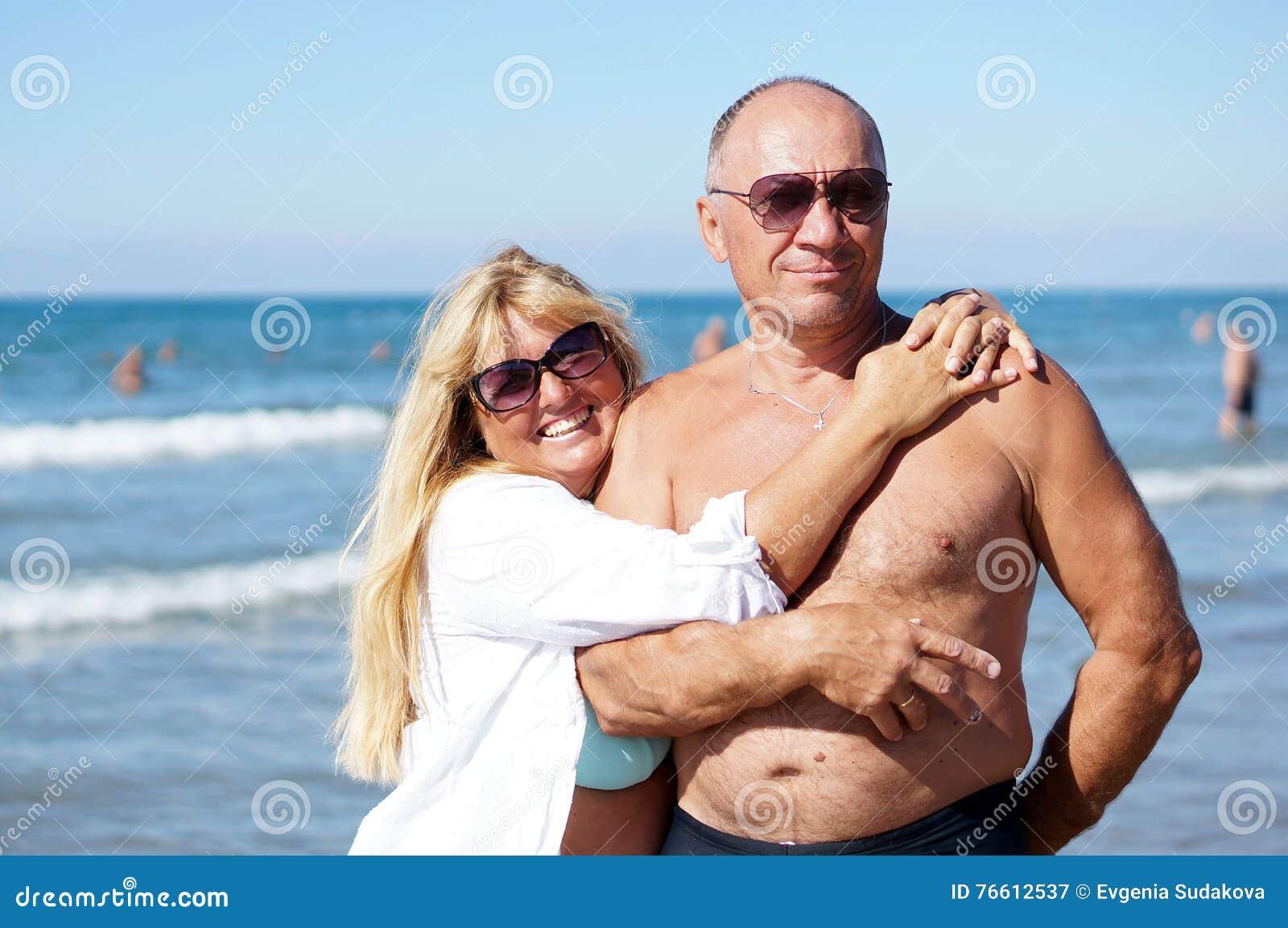Hög kvinna som kramar hennes make