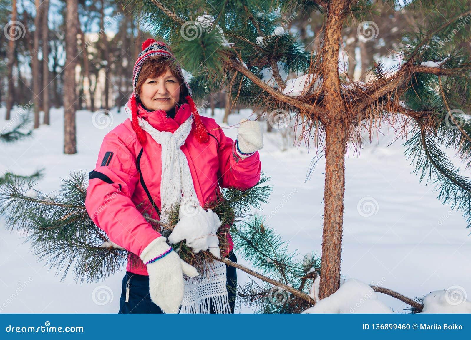 Hög kvinna som poserar vid granträdet på den soliga vinterdagen i skogen