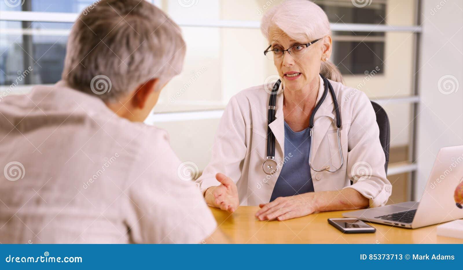 Hög kvinnadoktor som talar till den äldre patienten i kontoret