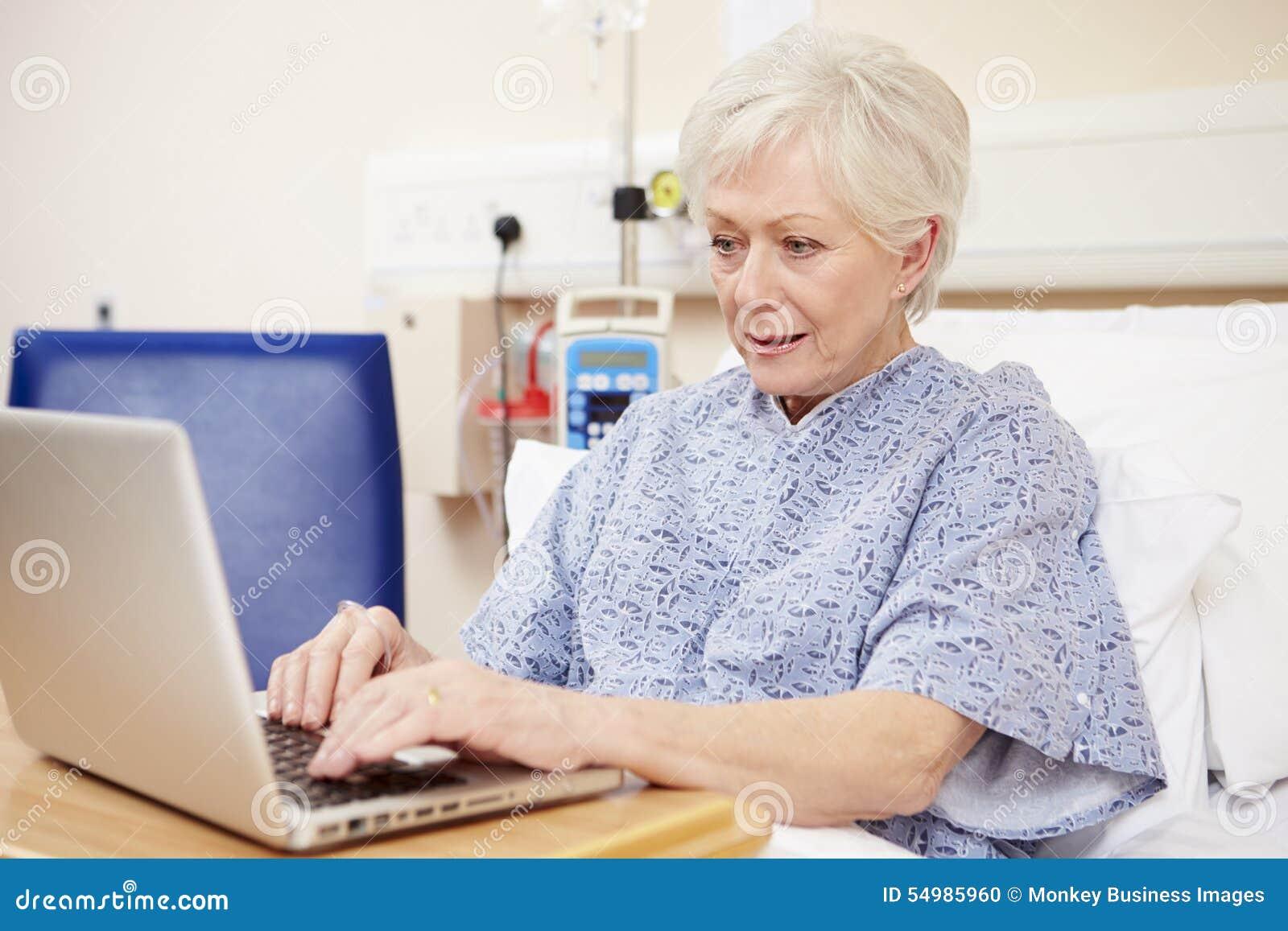 Hög kvinnlig tålmodig användande bärbar dator i sjukhussäng