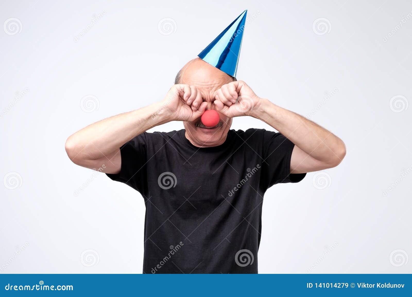 Hög man i födelsedaglocket som gråter och torkar revor på hans parti