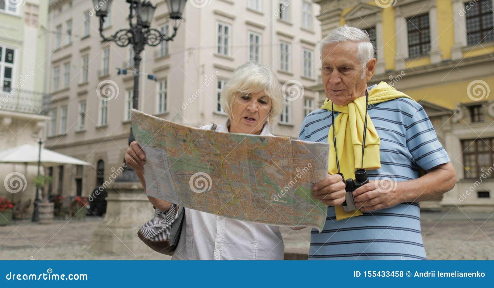 Hög man och kvinnliga turister som står med en översikt i händer som söker efter rutten