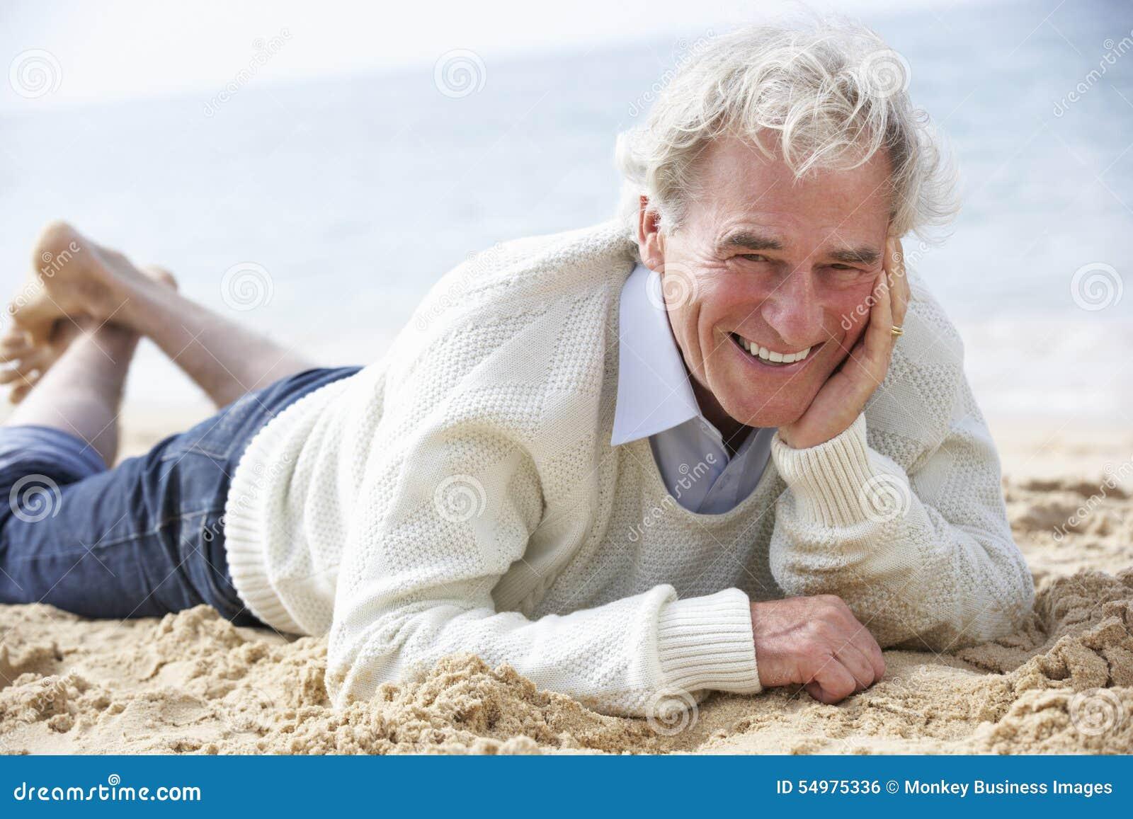 Hög man som kopplar av på stranden
