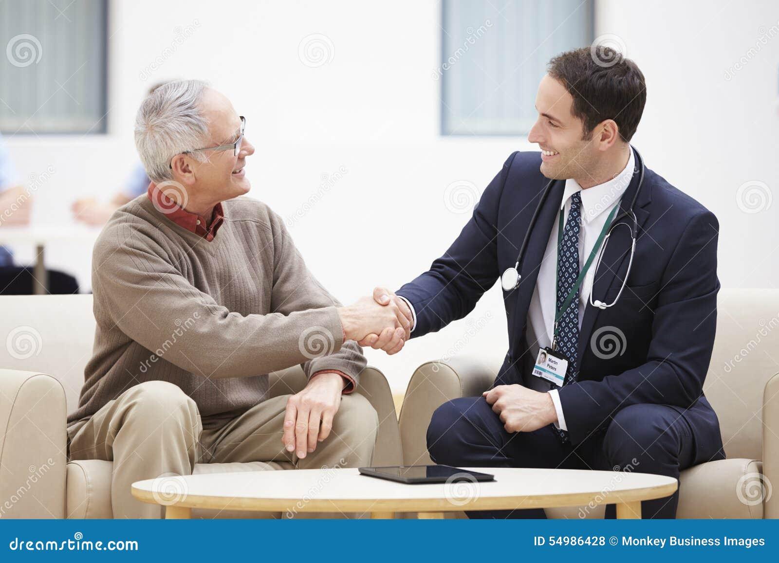 Hög man som skakar händer med doktorn