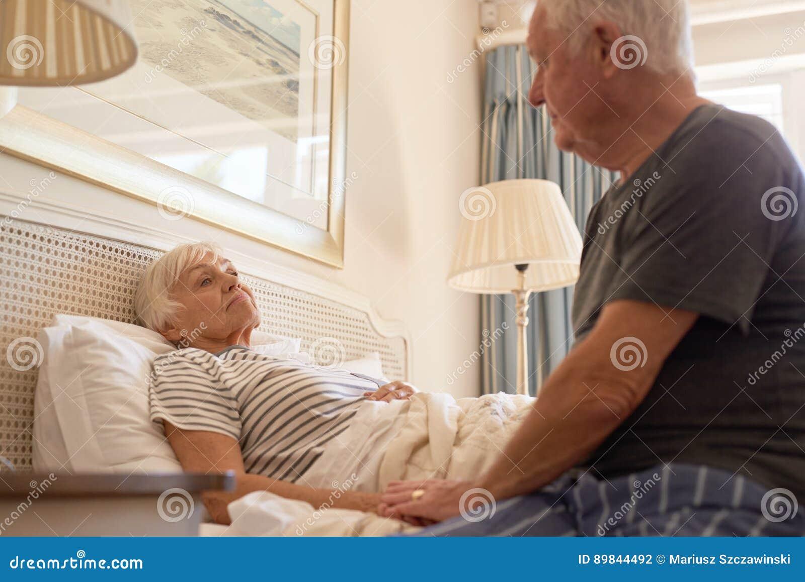 Hög man som tar omsorg av hans sjuka fru i säng
